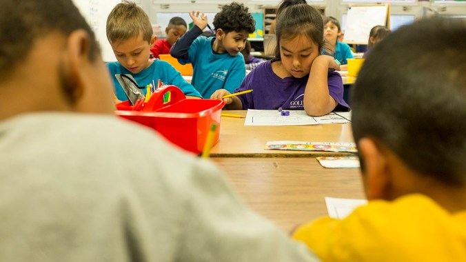 Students work at school desks.