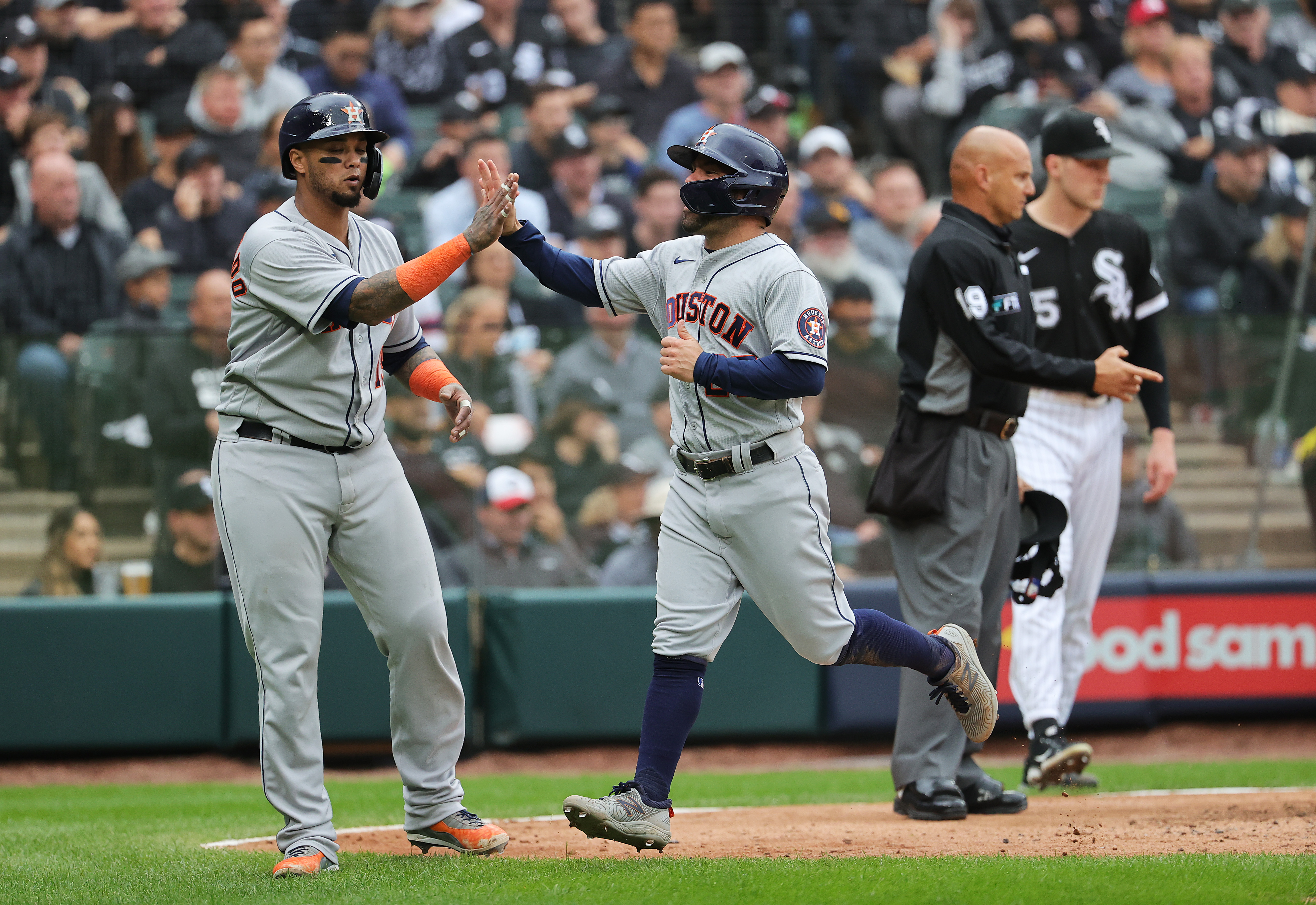 Jose Altuve #27 and Martin Maldonado #15 of the Houston Astros congratulate each other after scoring on a 2- RBI double by Alex Bregman #2 during the 4th inning of Game 4 of the American League Division Series against the Chicago White Sox at Guaranteed Rate Field on October 12, 2021 in Chicago, Illinois.
