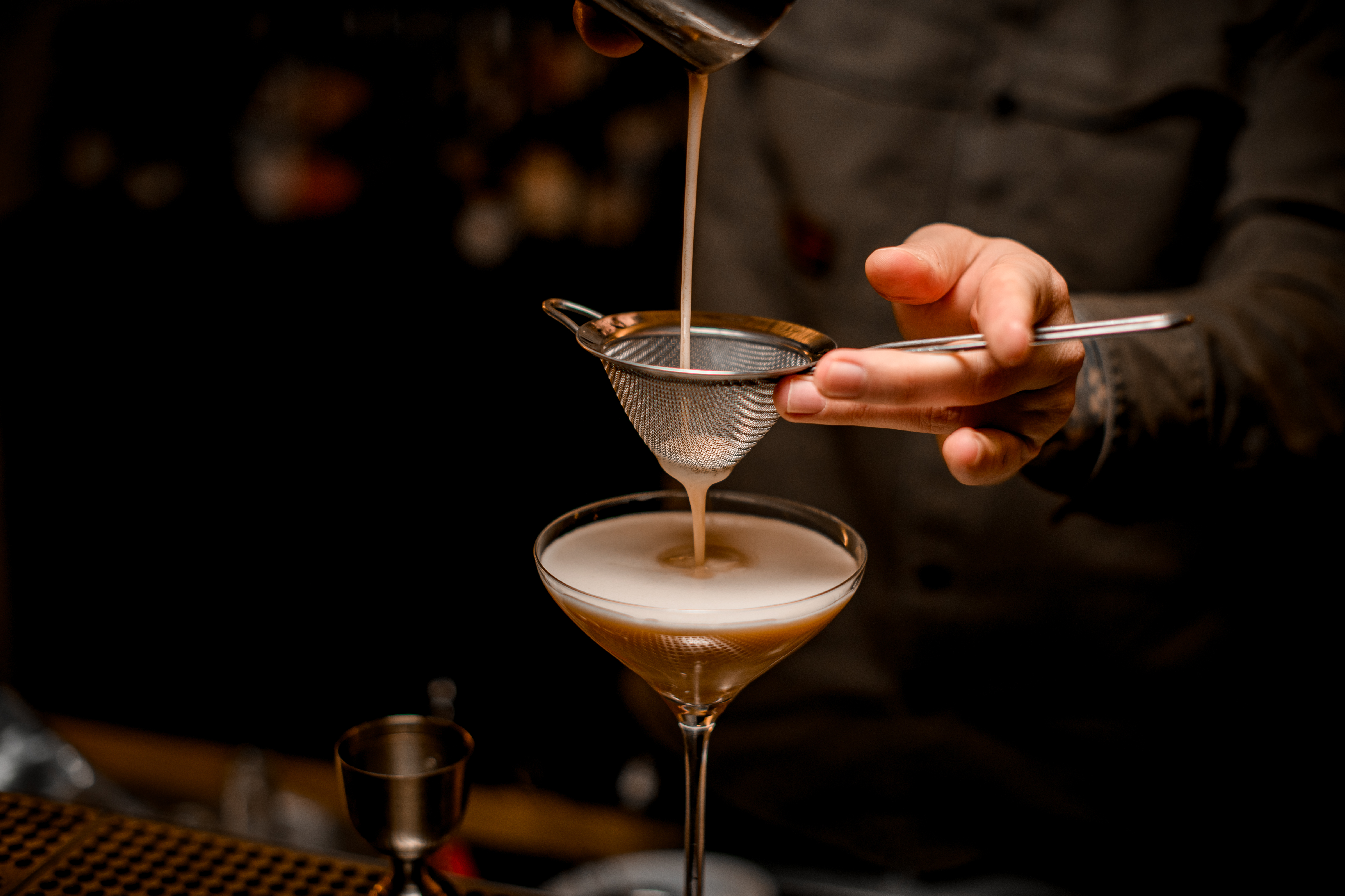 The hands and torso of a bartender in a black chef's coat, using a metal sieve to strain an espresso martini into a martini glass on a bar top.