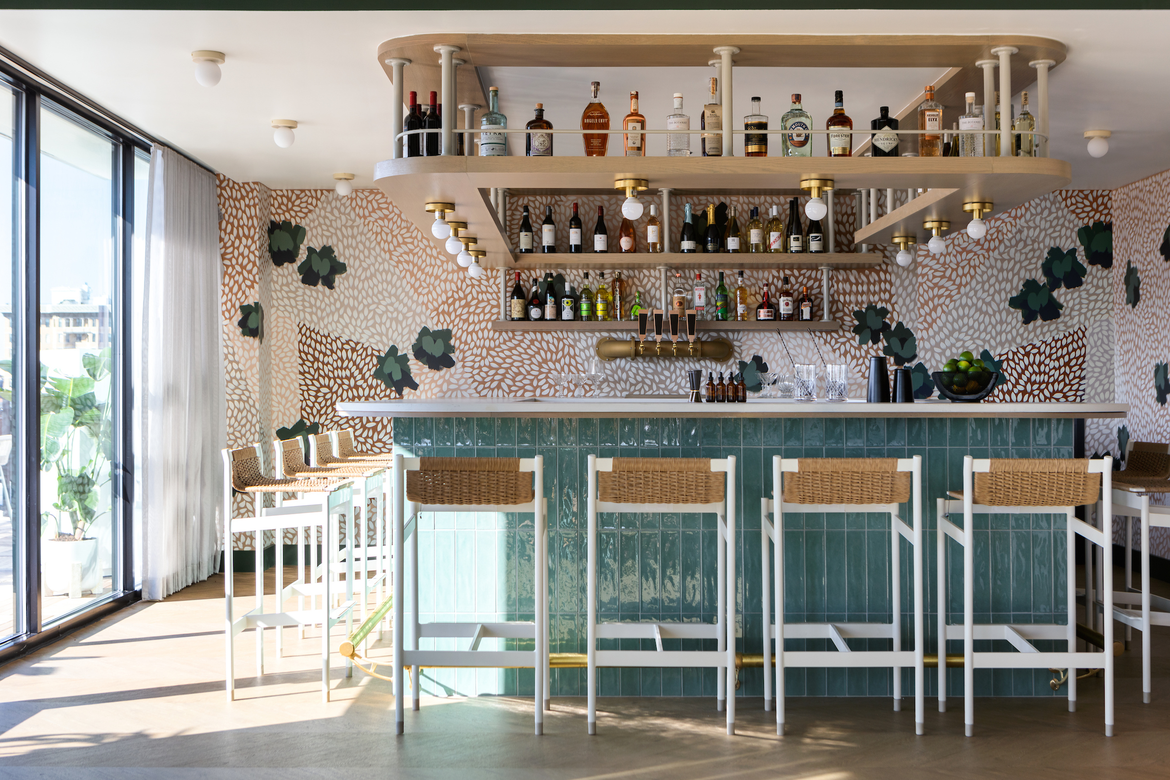 Lady Bird's bar is surrounded by teal accents and speckled wallpaper.