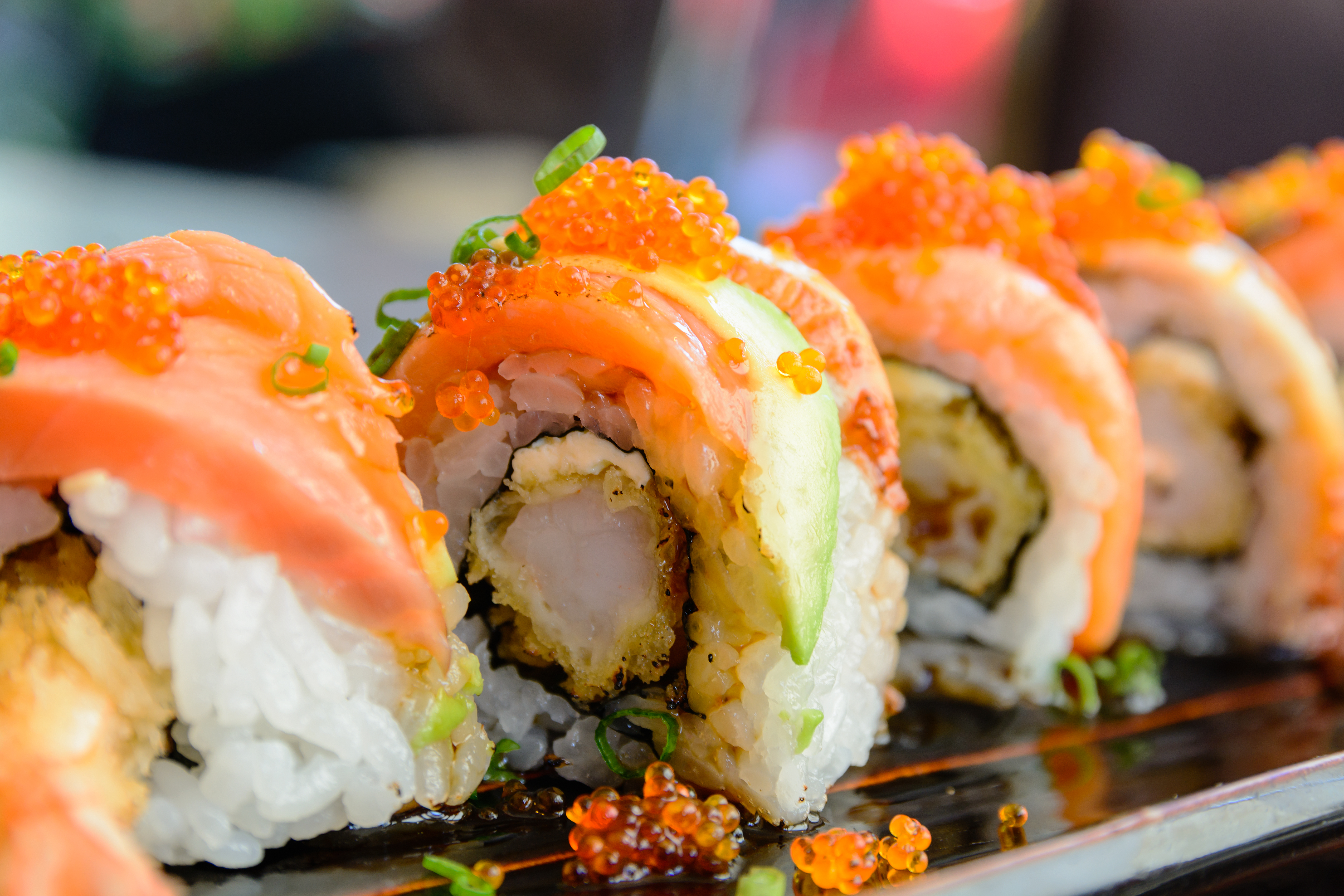 Sushi rolls filled with shrimp tempura and covered with strips of salmon.