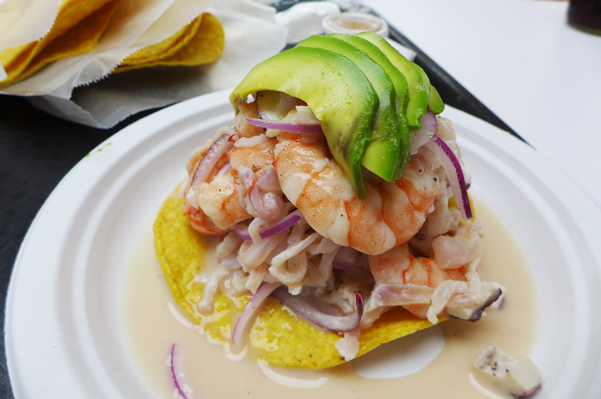 A round cracker with shrimp and other seafood piled high, topped with sliced and fanned avocado.
