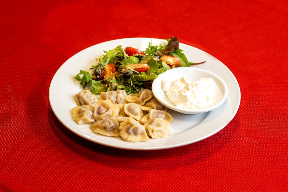 A plate of steamed little dumplings served with sour cream and a green salad.