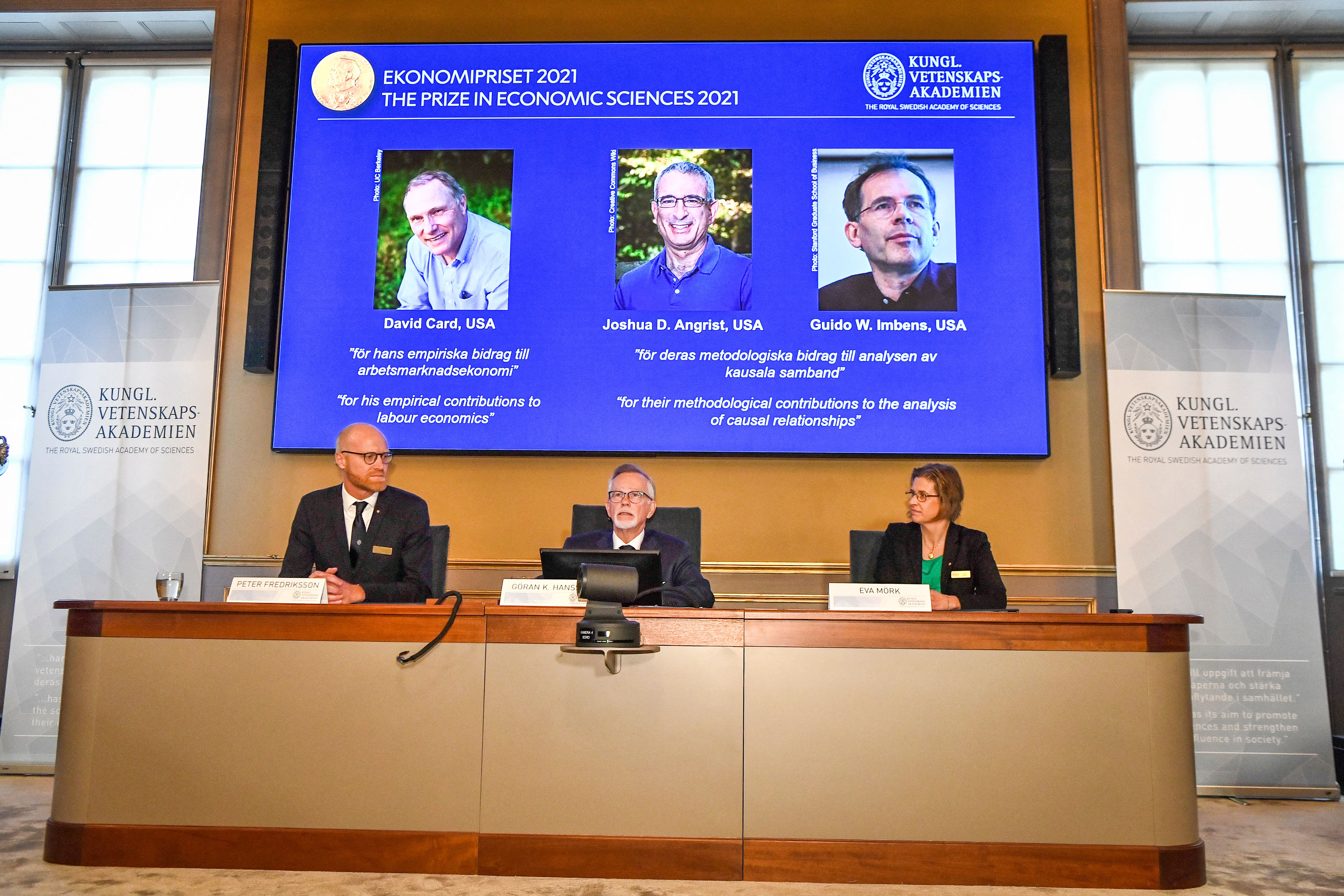 Three panelists of the Nobel Prize sit at a desk as a projector shows the winners of the Nobel Prize for Economics.