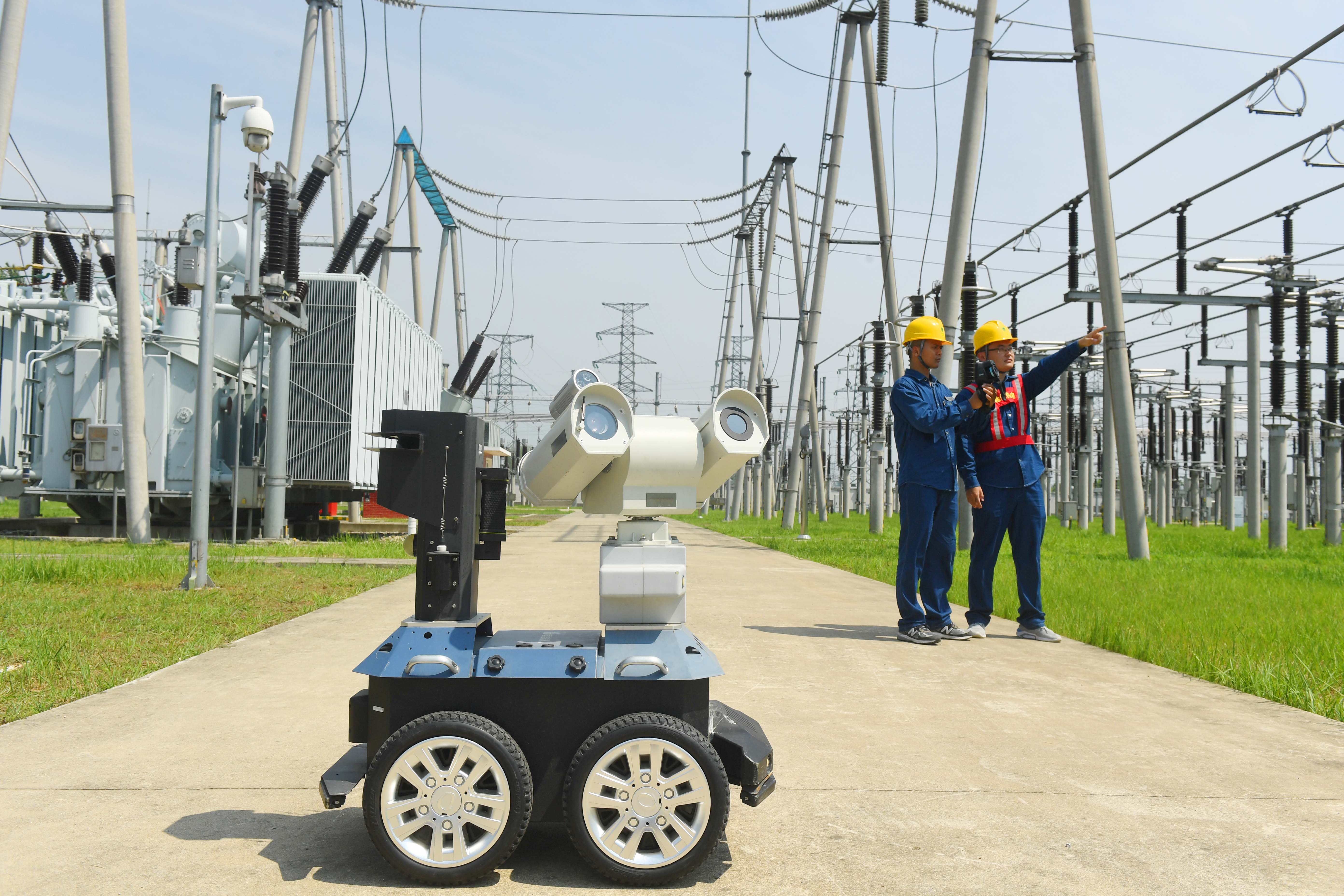 Two people in hard hats stand outside an electrical substation power facility behind a rolling robotic sensor.