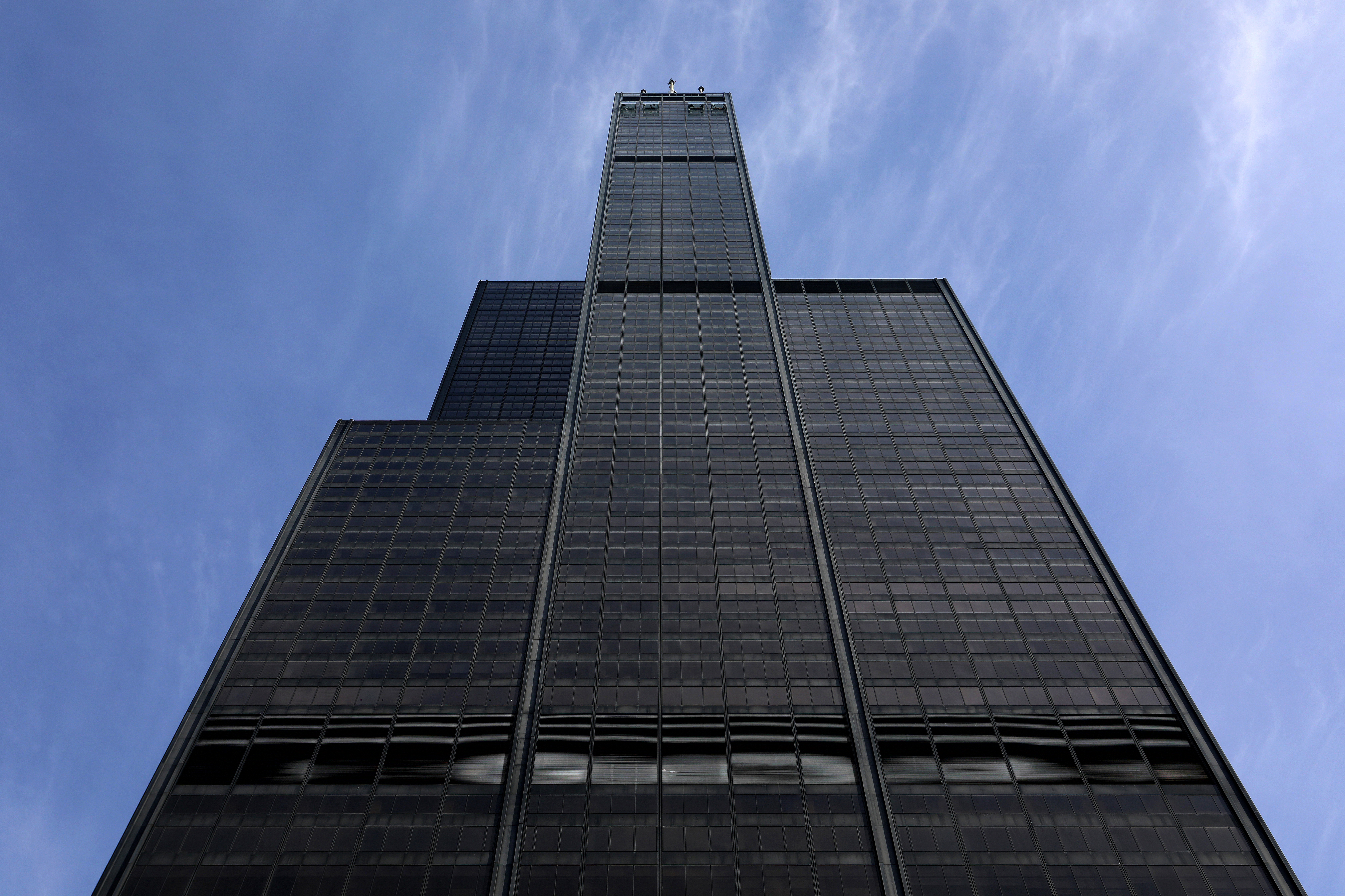 A view of a black skyscraper from the bottom looking all the way up
