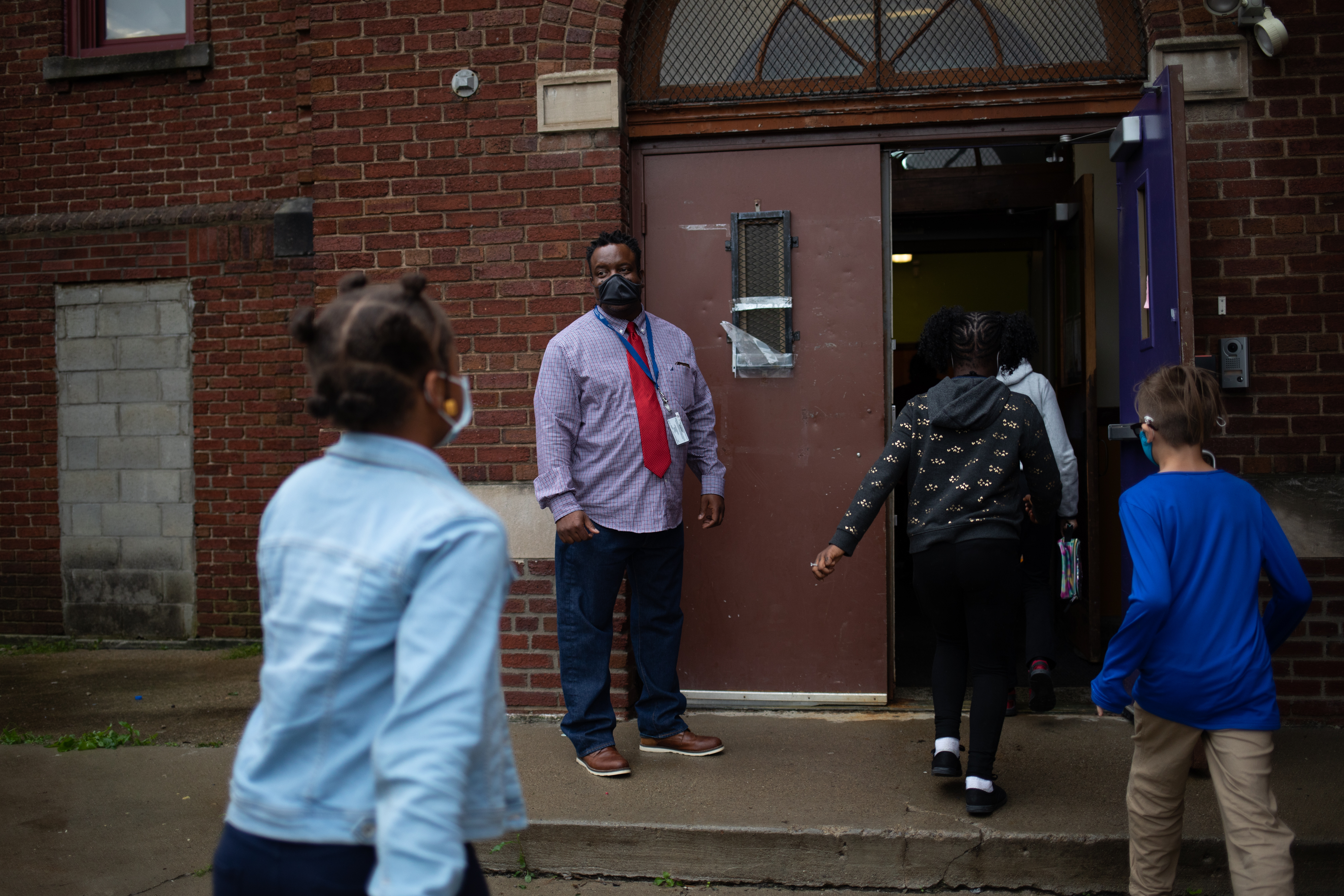 A teacher watches as students make their way into the brick facade of their school.
