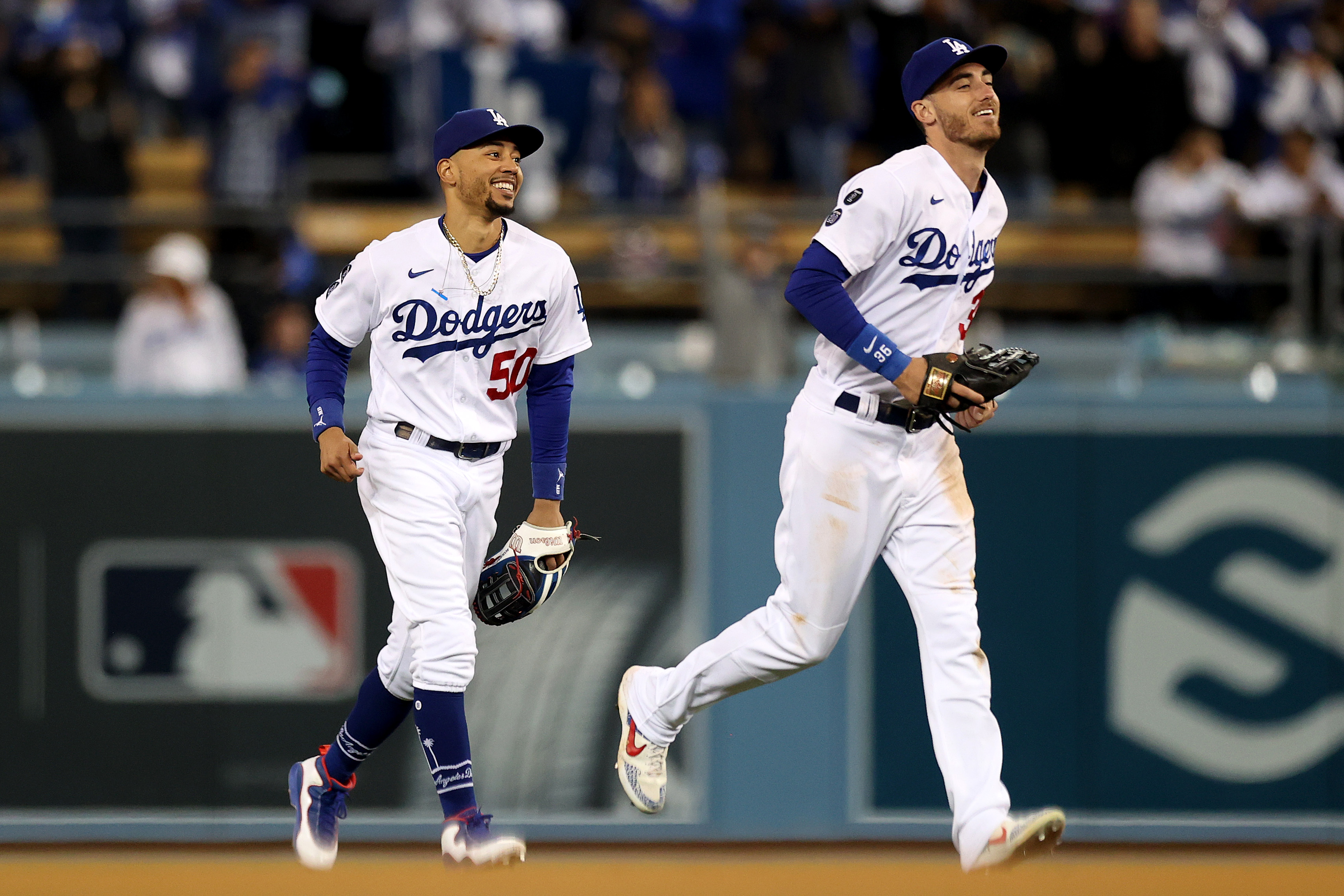 Cody Bellinger #35 and Mookie Betts #50 of the Los Angeles Dodgers react after beating the San Francisco Giants 7-2 in game 4 of the National League Division Series at Dodger Stadium on October 12, 2021 in Los Angeles, California.