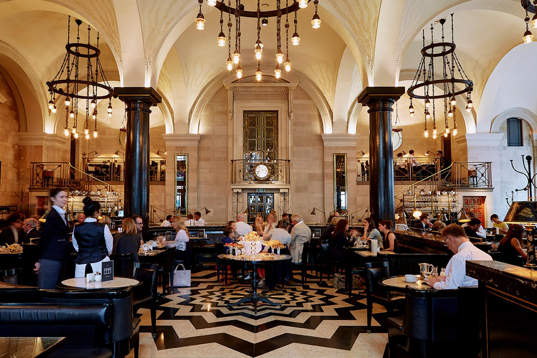 The dining room at the Wolseley in London, with a star-pattern tiled floor, black chandeliers hanging pendant bulbs, and two waiters standing attention.