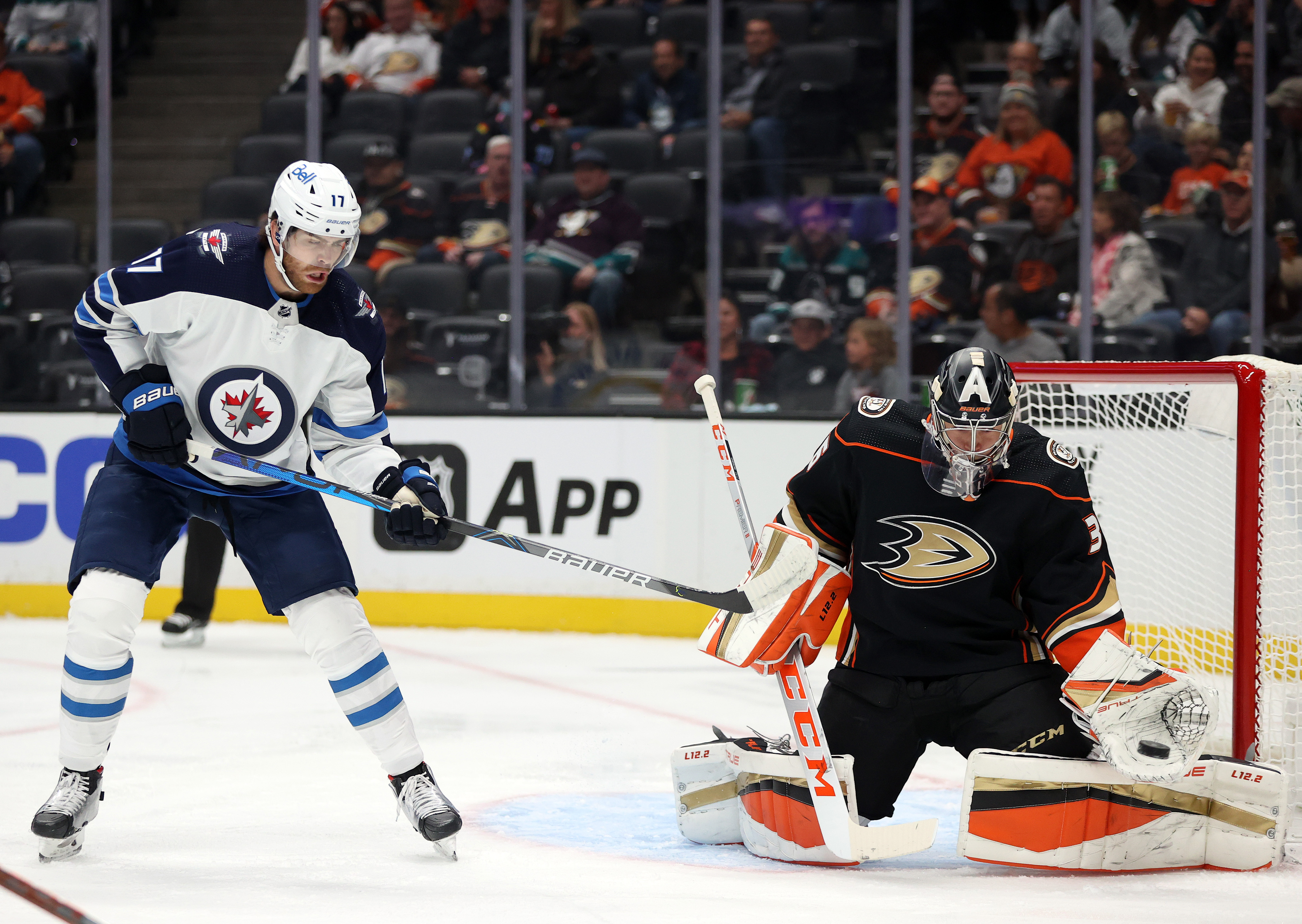 John Gibson #36 of the Anaheim Ducks makes a save in front of Adam Lowry #17 of the Winnipeg Jets in the first period at Honda Center on October 13, 2021 in Anaheim, California.