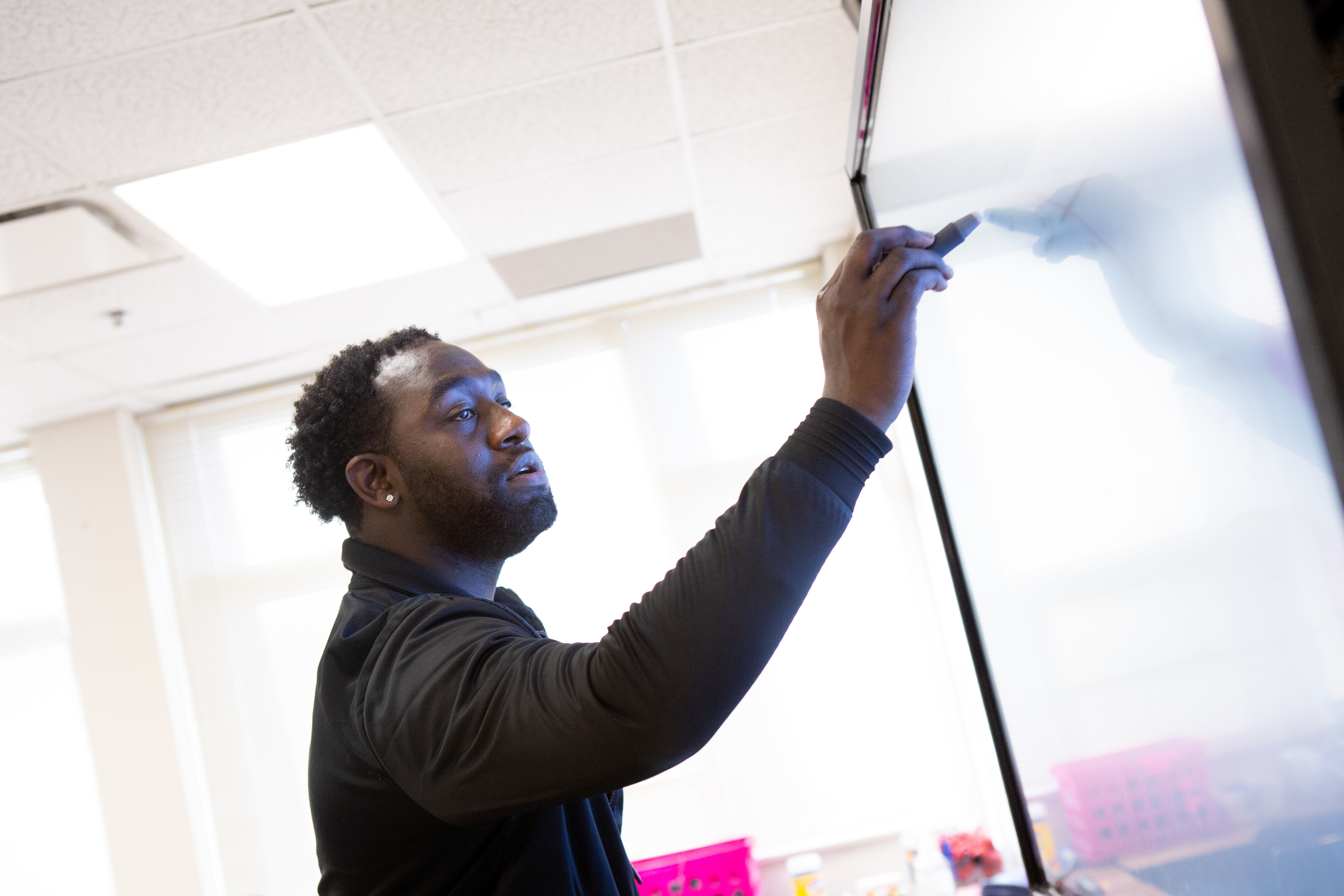 A teacher writes on a white board with a marker inside a bright sunny classroom.
