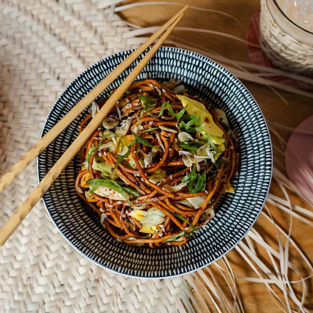 A bowl of noodles slathered in a reddish sauce, and garnished with green vegetables.