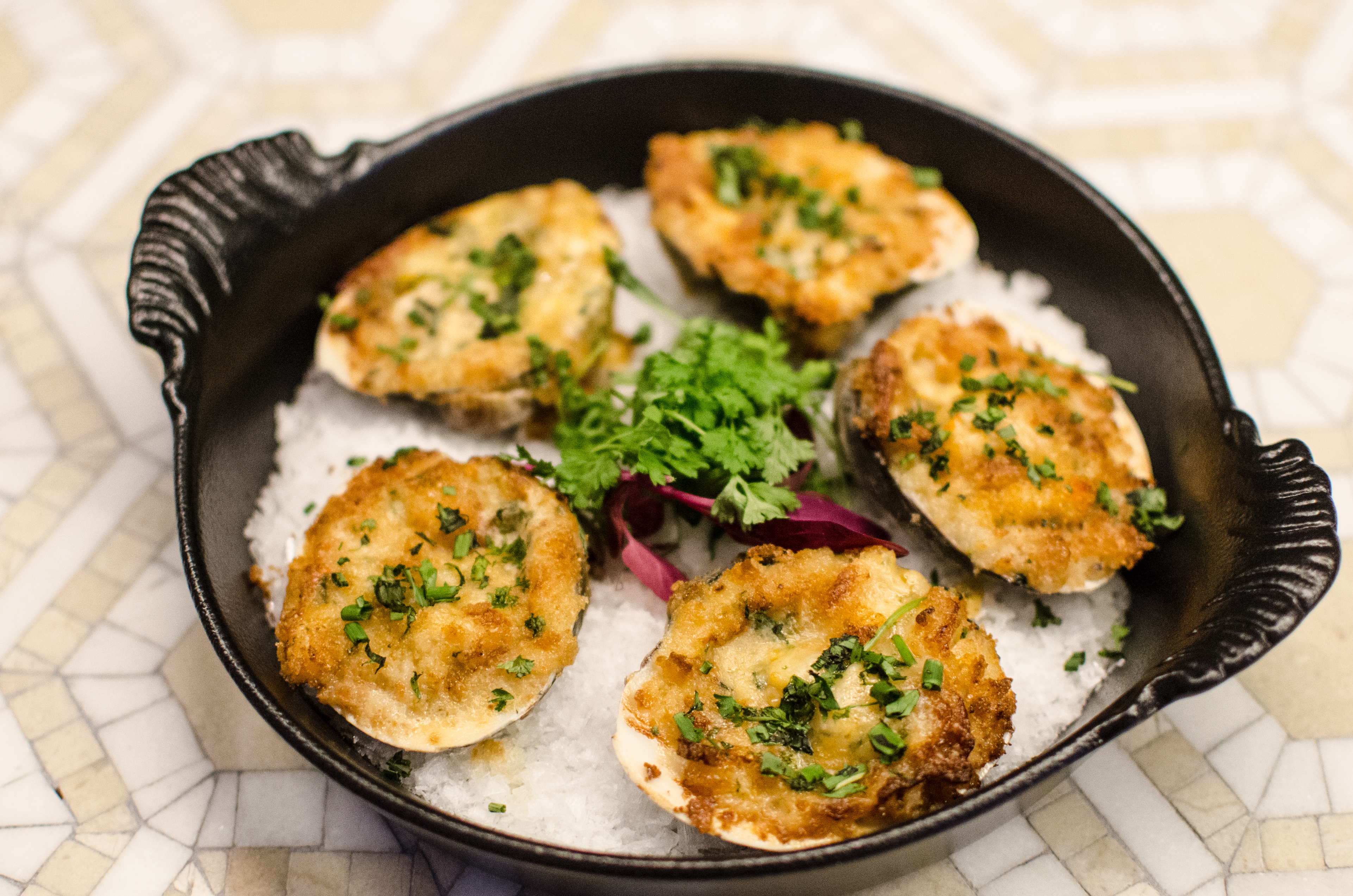 Baked clams topped with cheese, herbs, and spices are arranged on a bed of salt in a small cast iron pan.