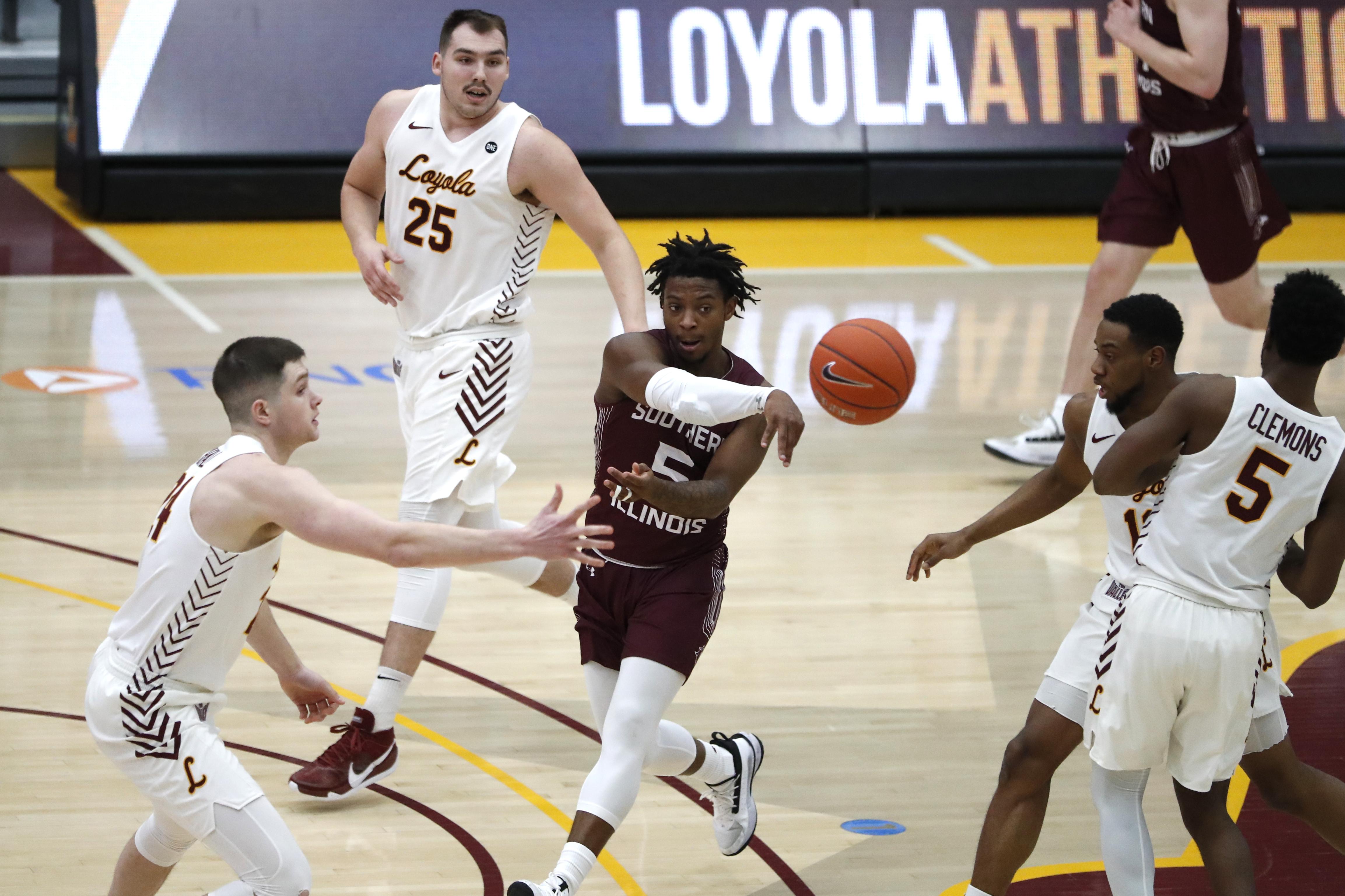 Southern Illinois guard Lance Jones, center, passes the ball through Loyola defenders.