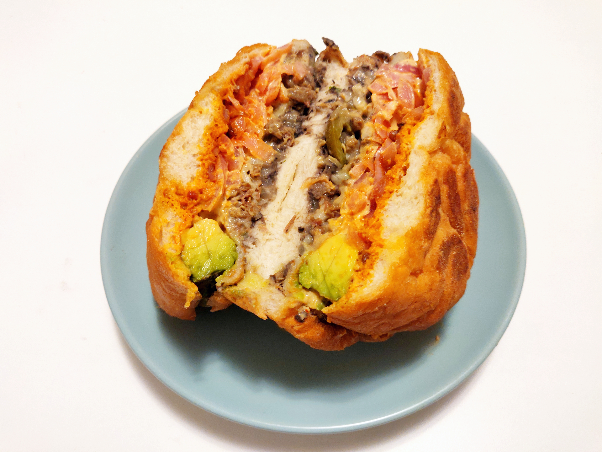A thick Mexican sandwich is cut open and sits on a blue plate on a light background.