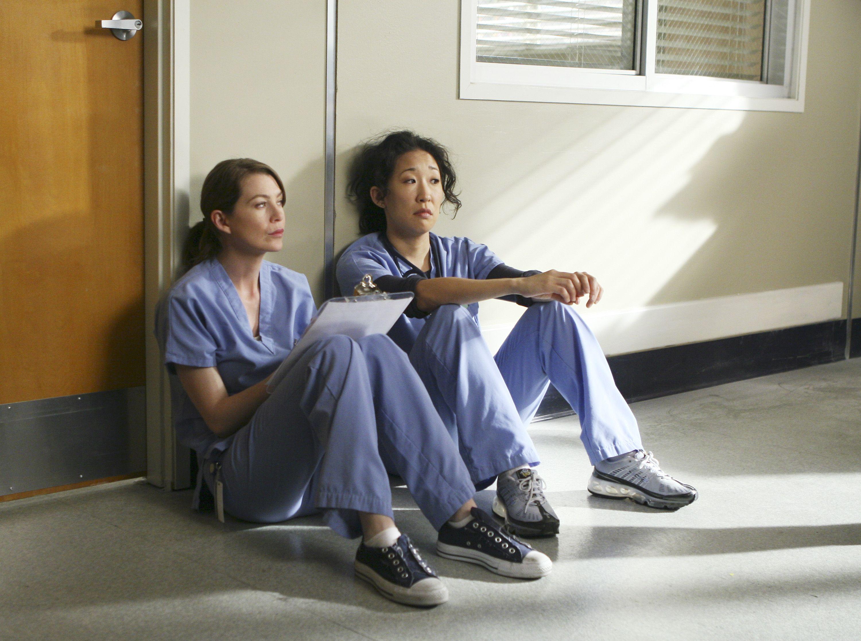 Dr. Meredith Grey (Ellen Pompeo) and Dr. Cristina Yang (Sandra Oh) sit side by side on the hospital floor.