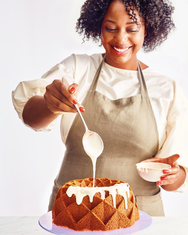 A woman drizzles a glaze over a geometric bundt cake