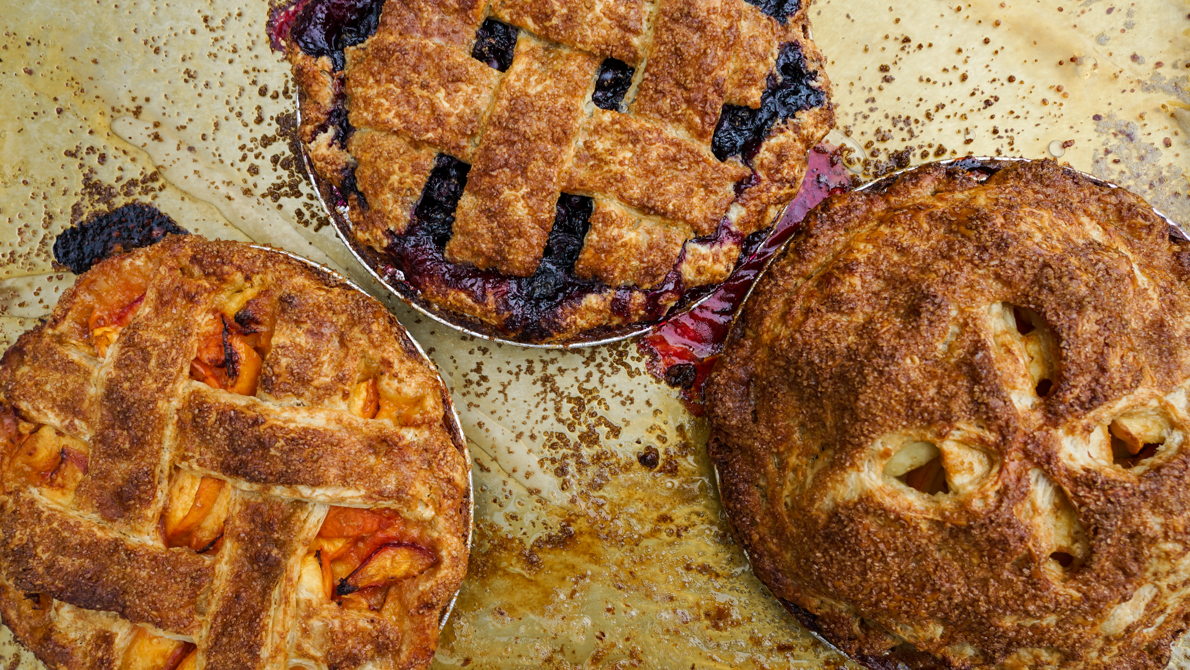 Three pies arranged and shot overhead with a baking sheet beneath.