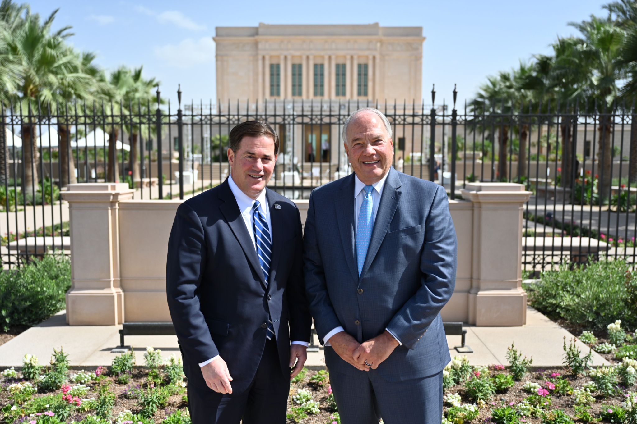 Arizona Gov. Doug Ducey and Elder Ronald A. Rasband stop for a photo in front of the newly renovated Mesa Arizona Temple.