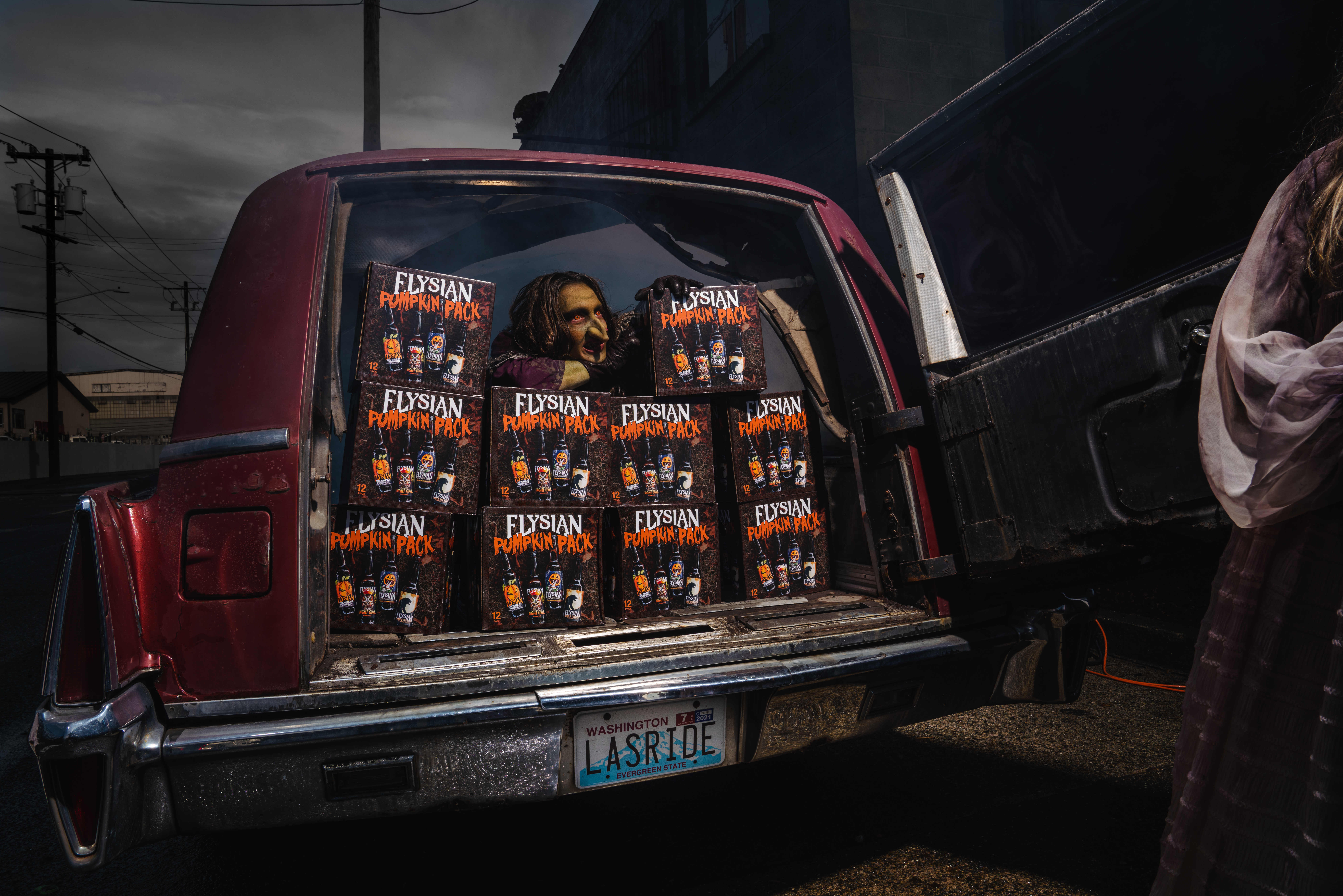A ghoulish figure with red eyes and green skin peers from over a wall of beers in the back of a vehicle.
