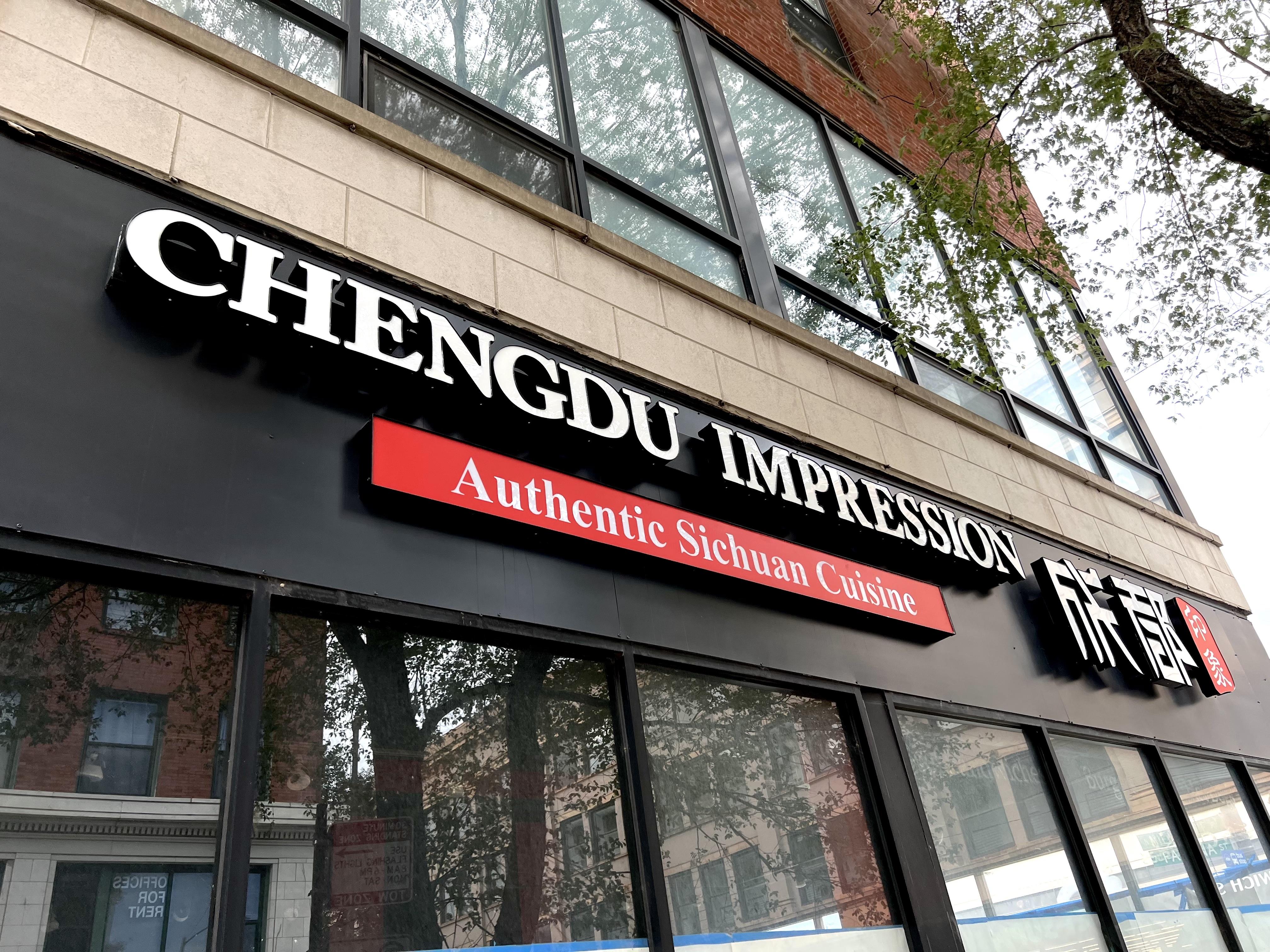 "A restaurant sign above windows reading ""Chengdu Impression"" in white over black."