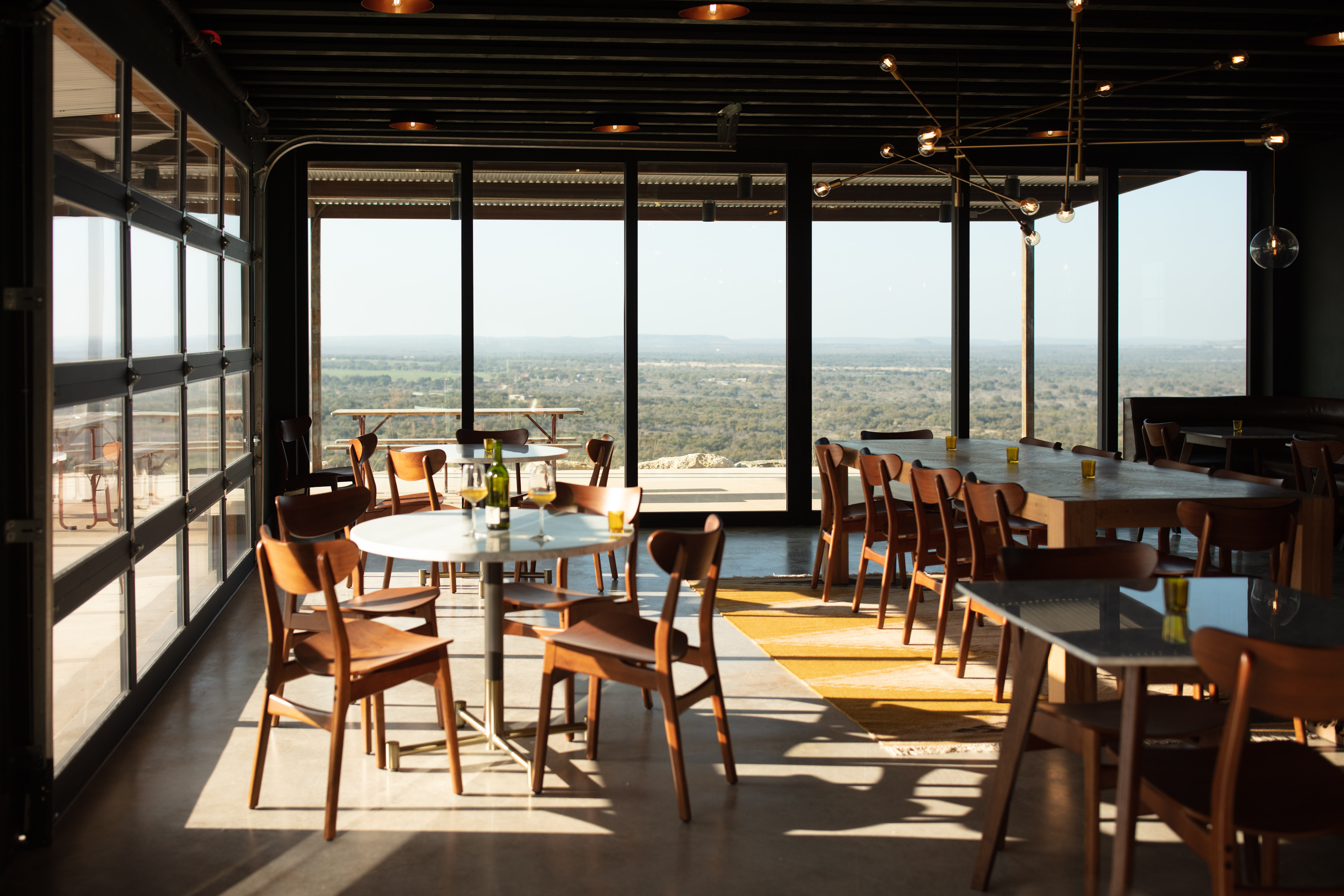 A restaurant dining room with a circular table and a long table with chairs surrounded by tall windows facing a sprawling landscape.