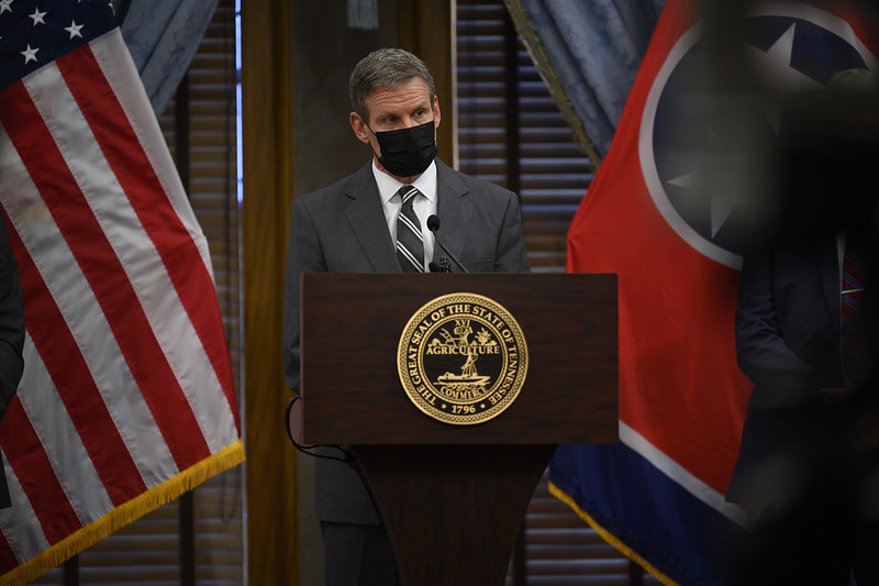 Tennessee Gov. Bill Lee stands alone and masked a podium with the U.S. flag to his left and the state flag to his right.