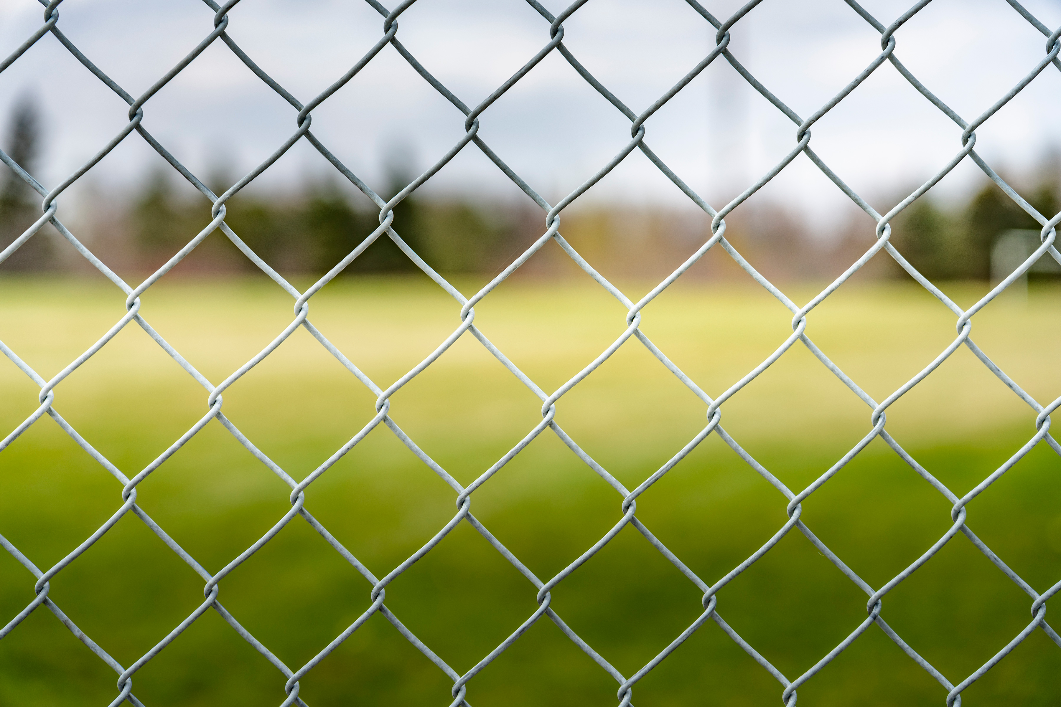 Looking through a chain link fence onto an open field.