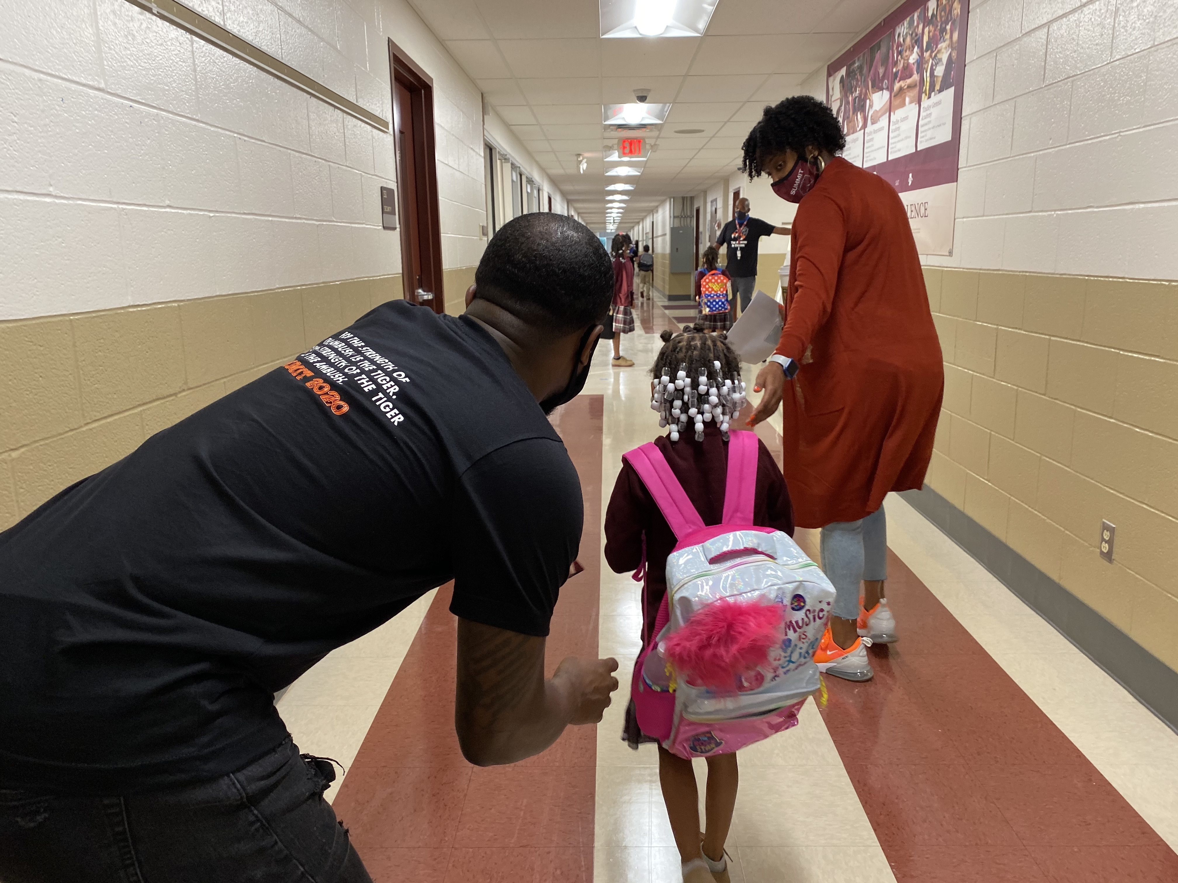 A masked woman in a long orange sweater guides a child carrying a pink backpack down a school hall, while a man in a black T-shirt bends down slightly behind the child.
