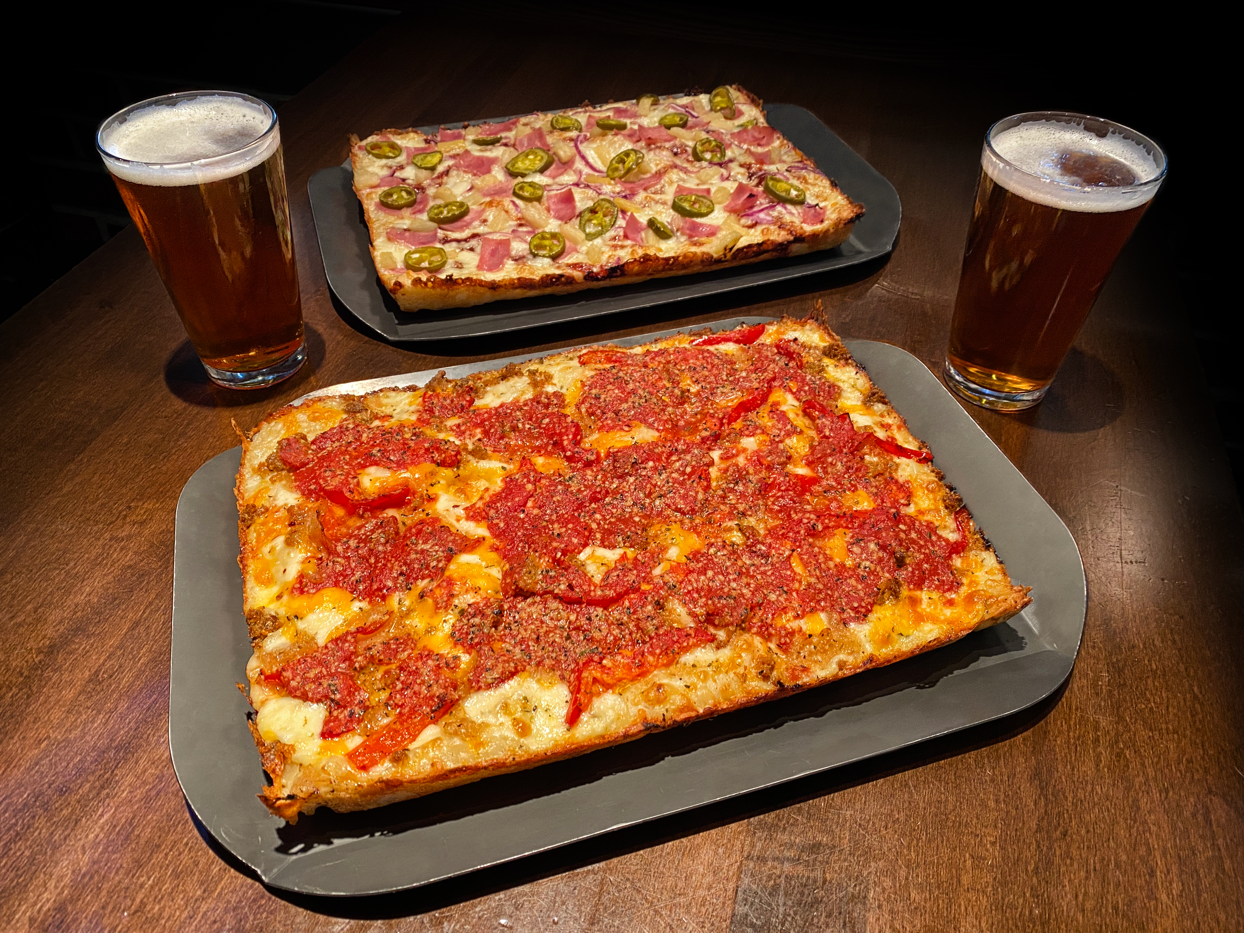 Two square pizzas (Oktoberfest and Hawaiian) are flanked by two glasses of dark beer
