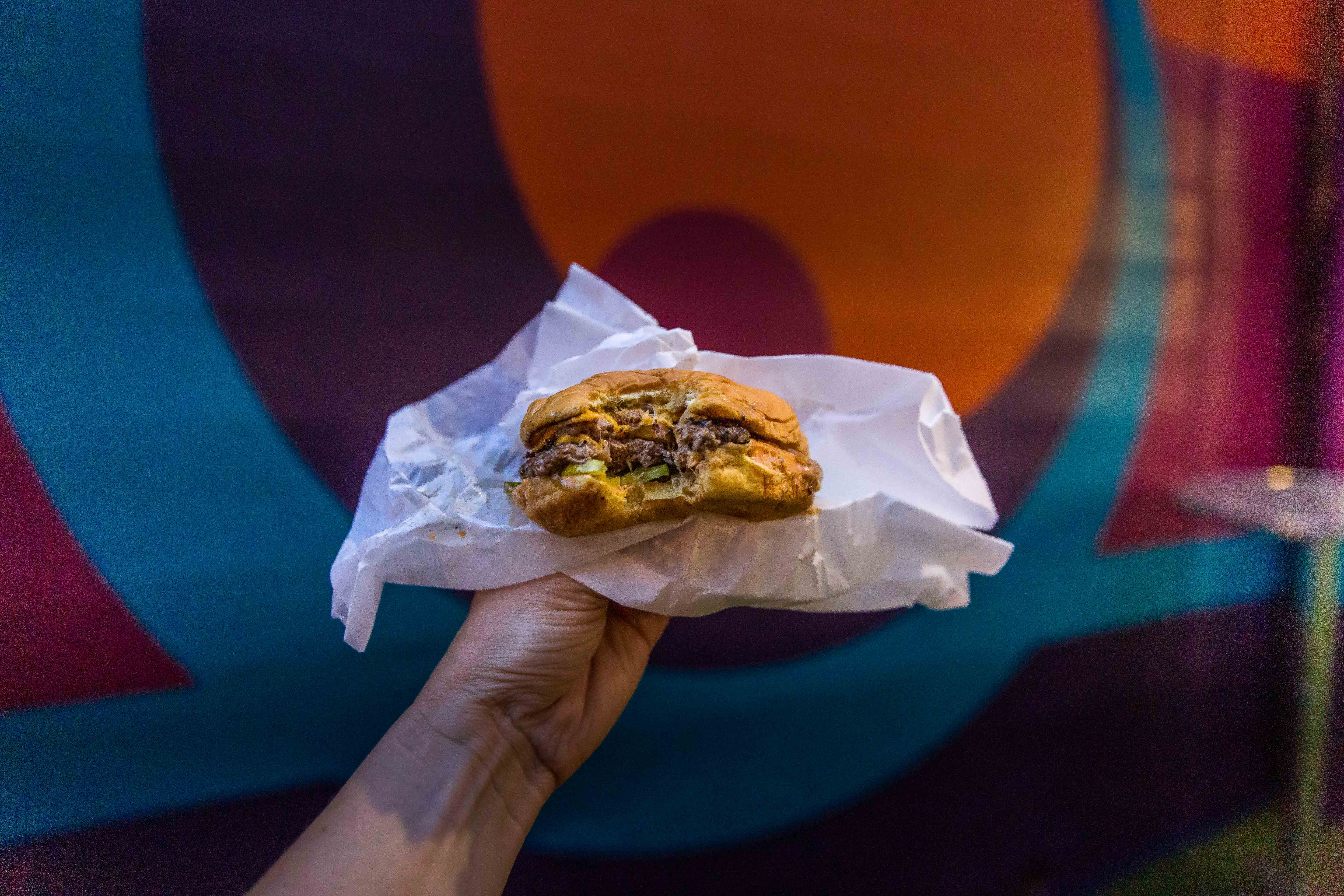 Hand holding a cheeseburger in front of a mural.