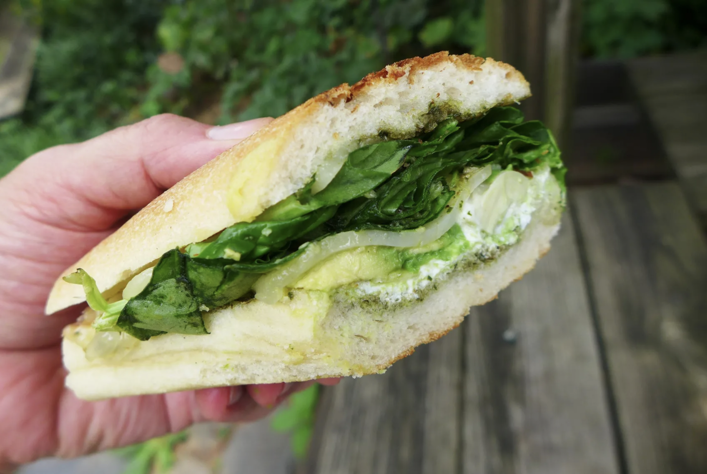 """The """"Green Machine"""" sandwich at Barnyard Cheese Shop is held in-hand. Inside there's pesto, artichokes, goat cheese, spinach, and cheddar on a roll."""