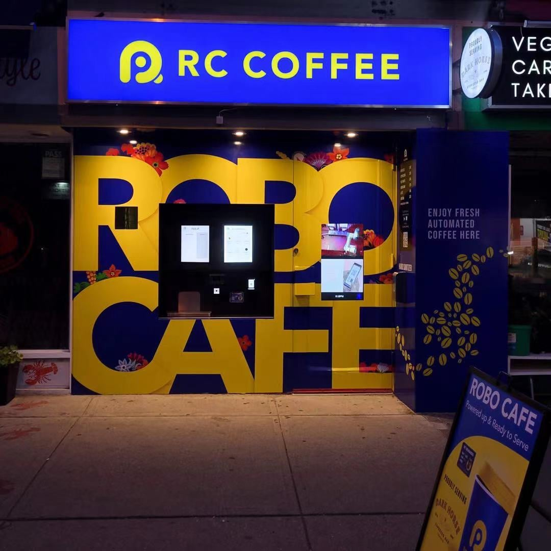 A coffee kiosk in the middle of the words ROBO CAFE.
