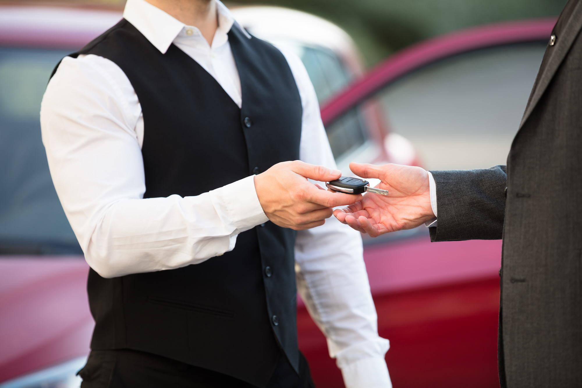 a person in a white shirt and black vest hands over a set of keys