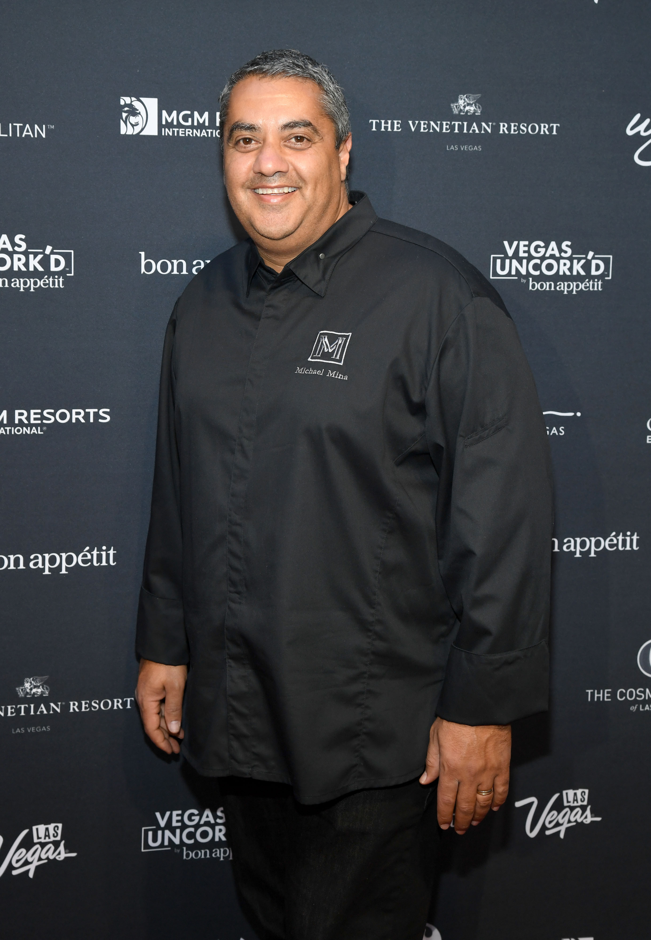 Chef stands in front of a step-and-repeat wearing black coat.