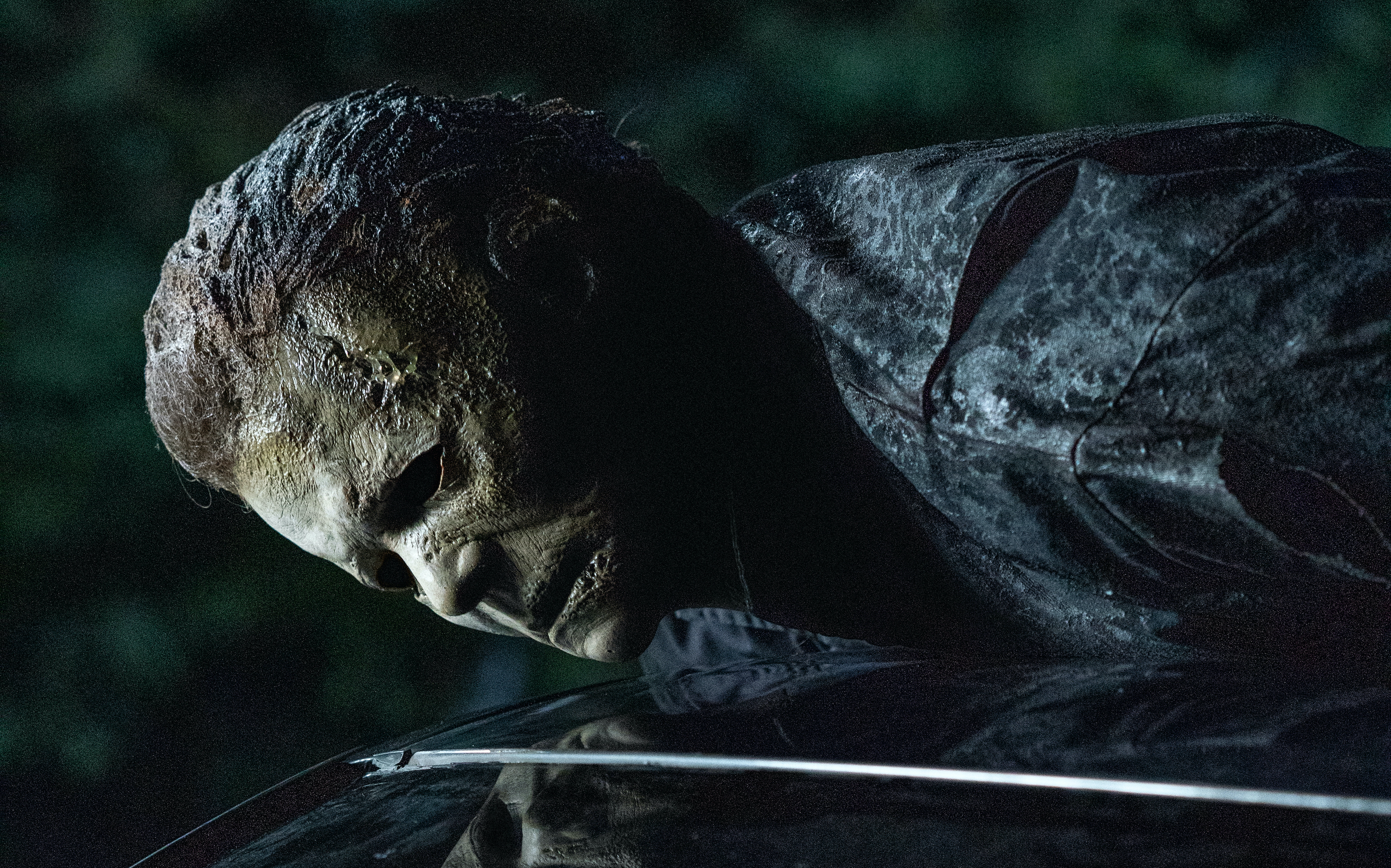 Masked killer Michael Myers lies on top of a car and looms over the victim inside in Halloween Kills