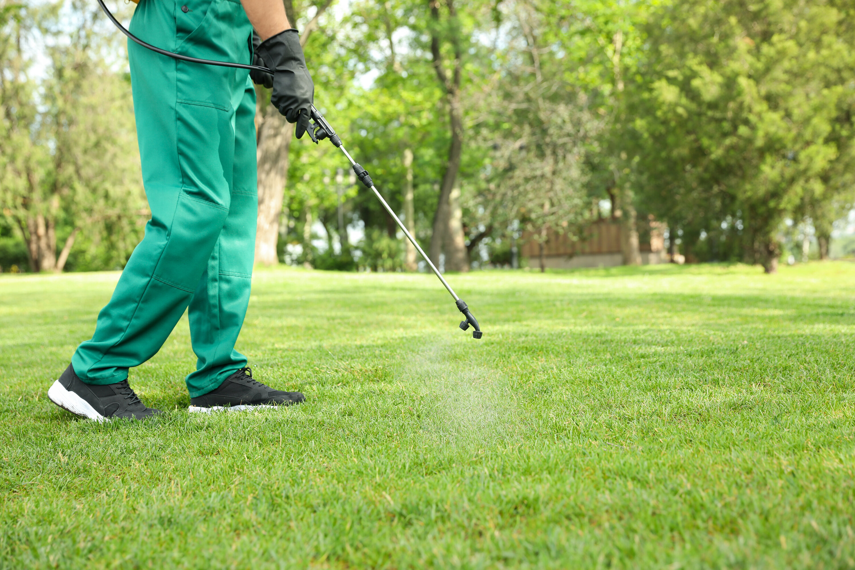 Worker in green exterminator gear spraying pesticide into the grass