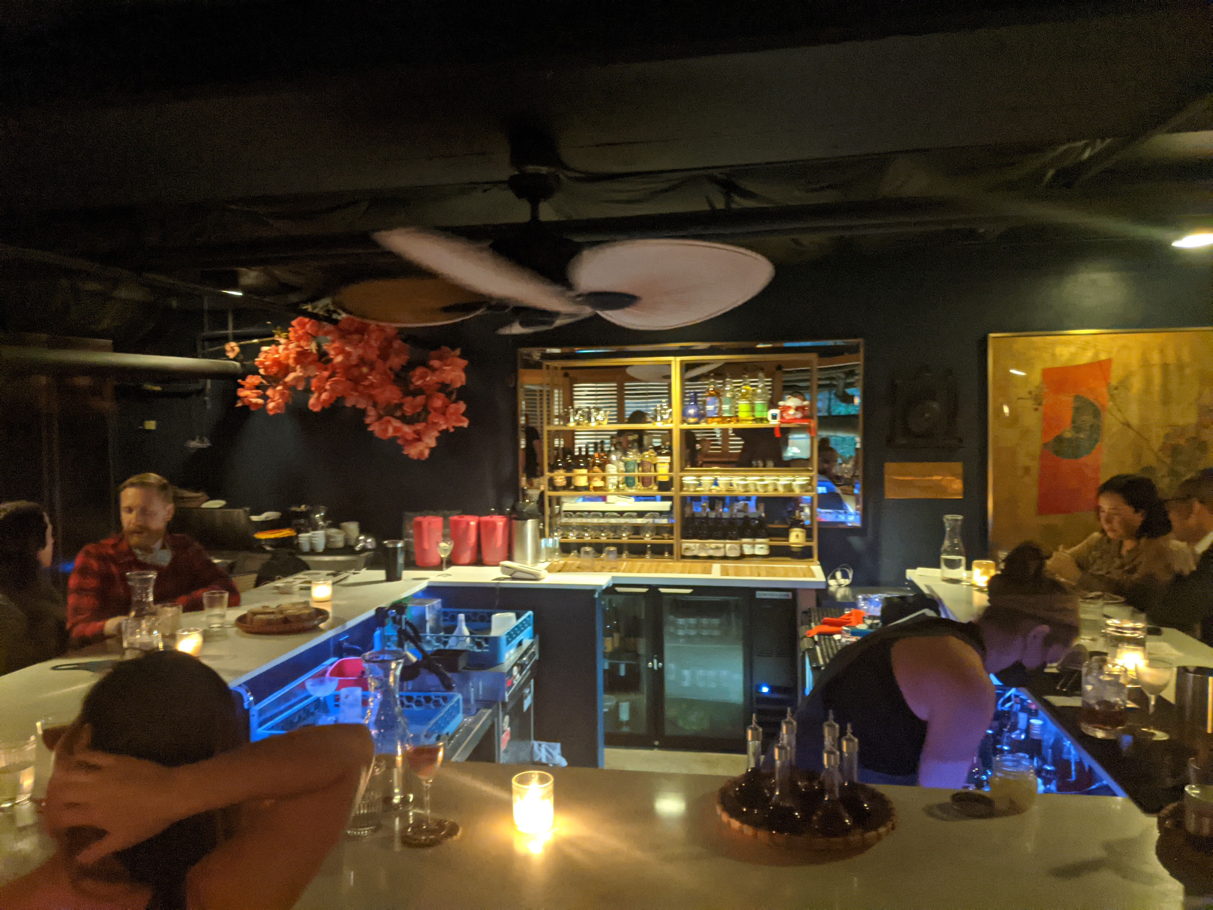 A square-shaped bar with white counters and candles. There are bright orange blossoms in the corner of the dimly-lit room.