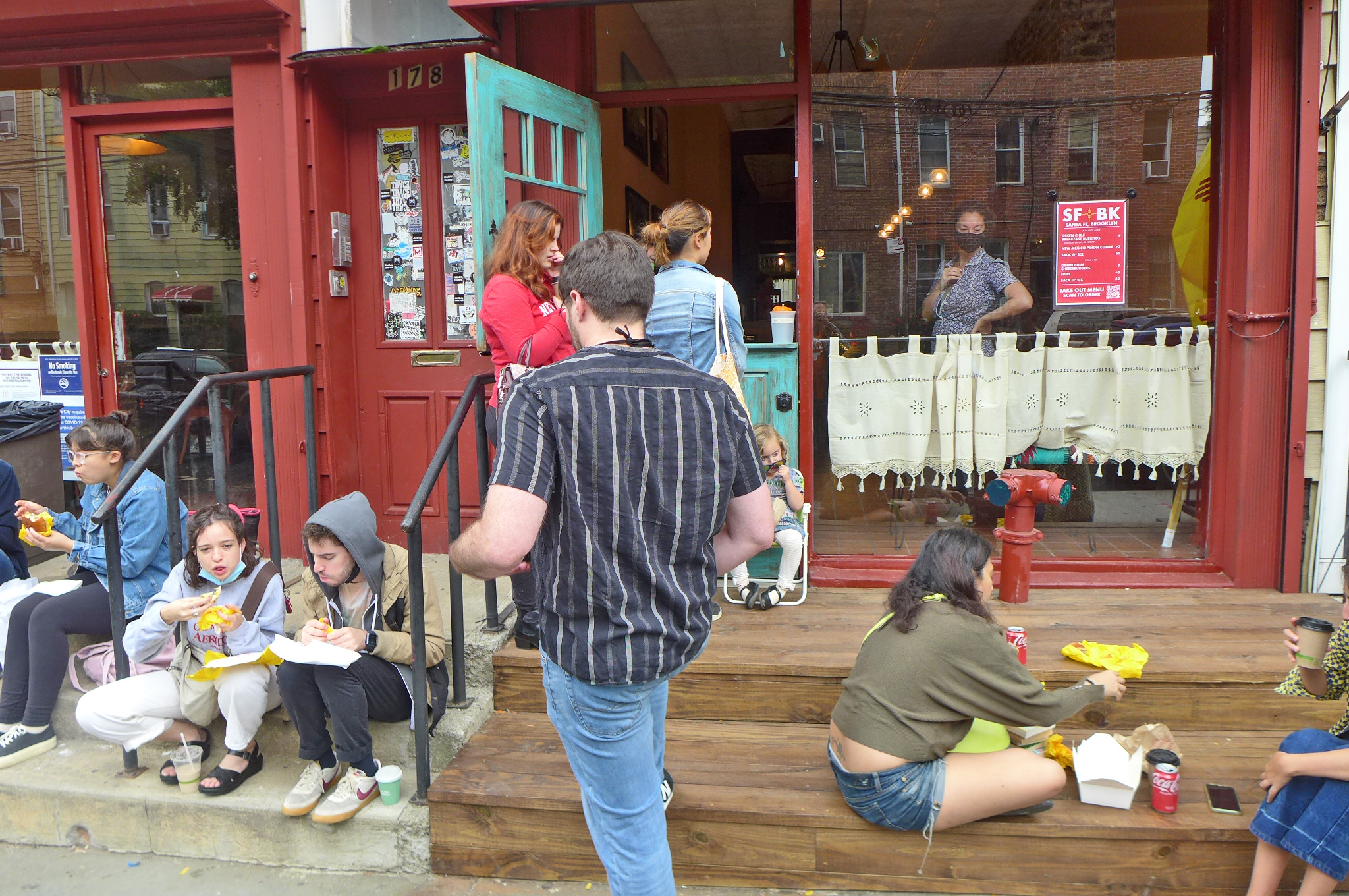 A front porch with several people eating.