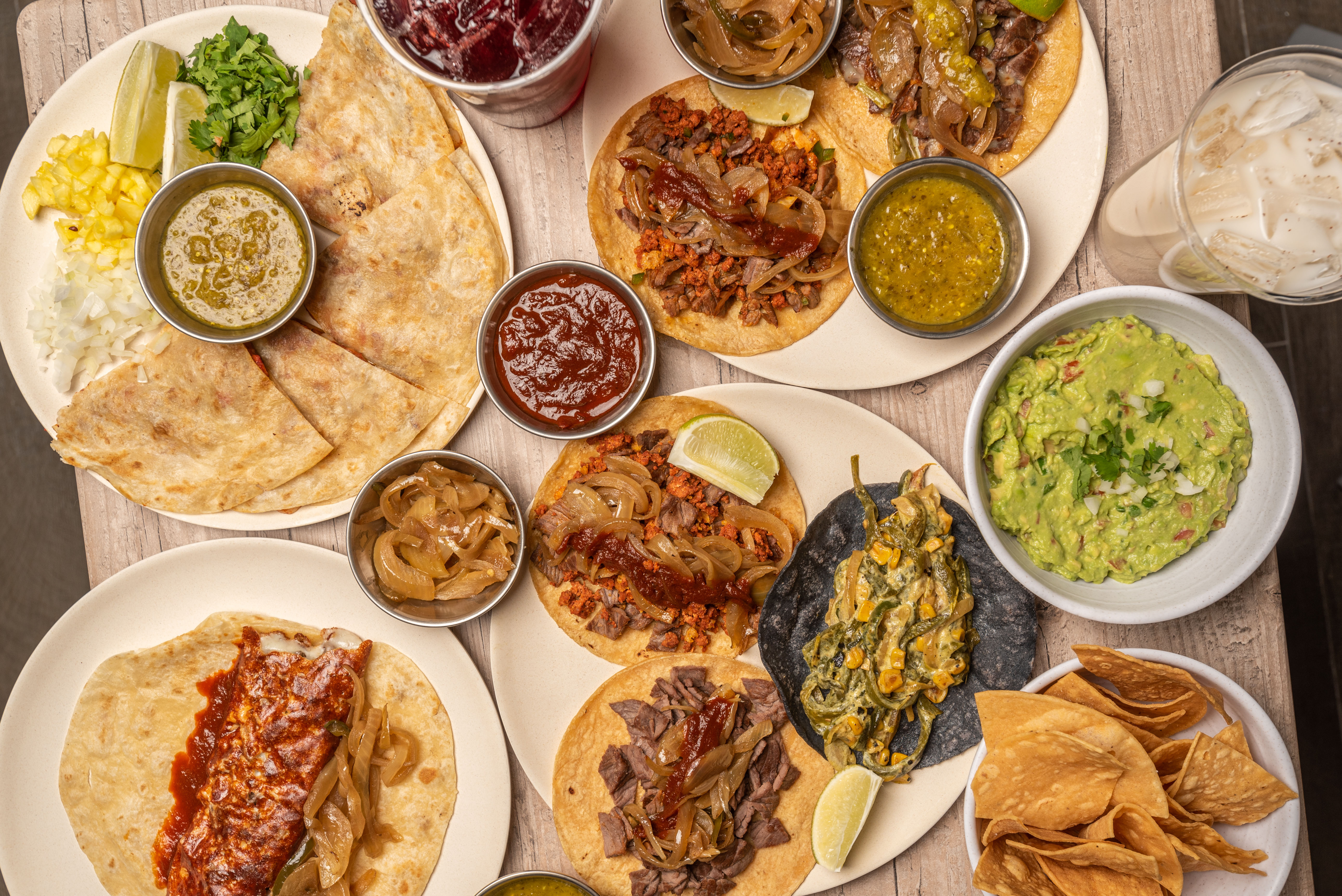 Tacos and other Mexican dishes laid out on a table.