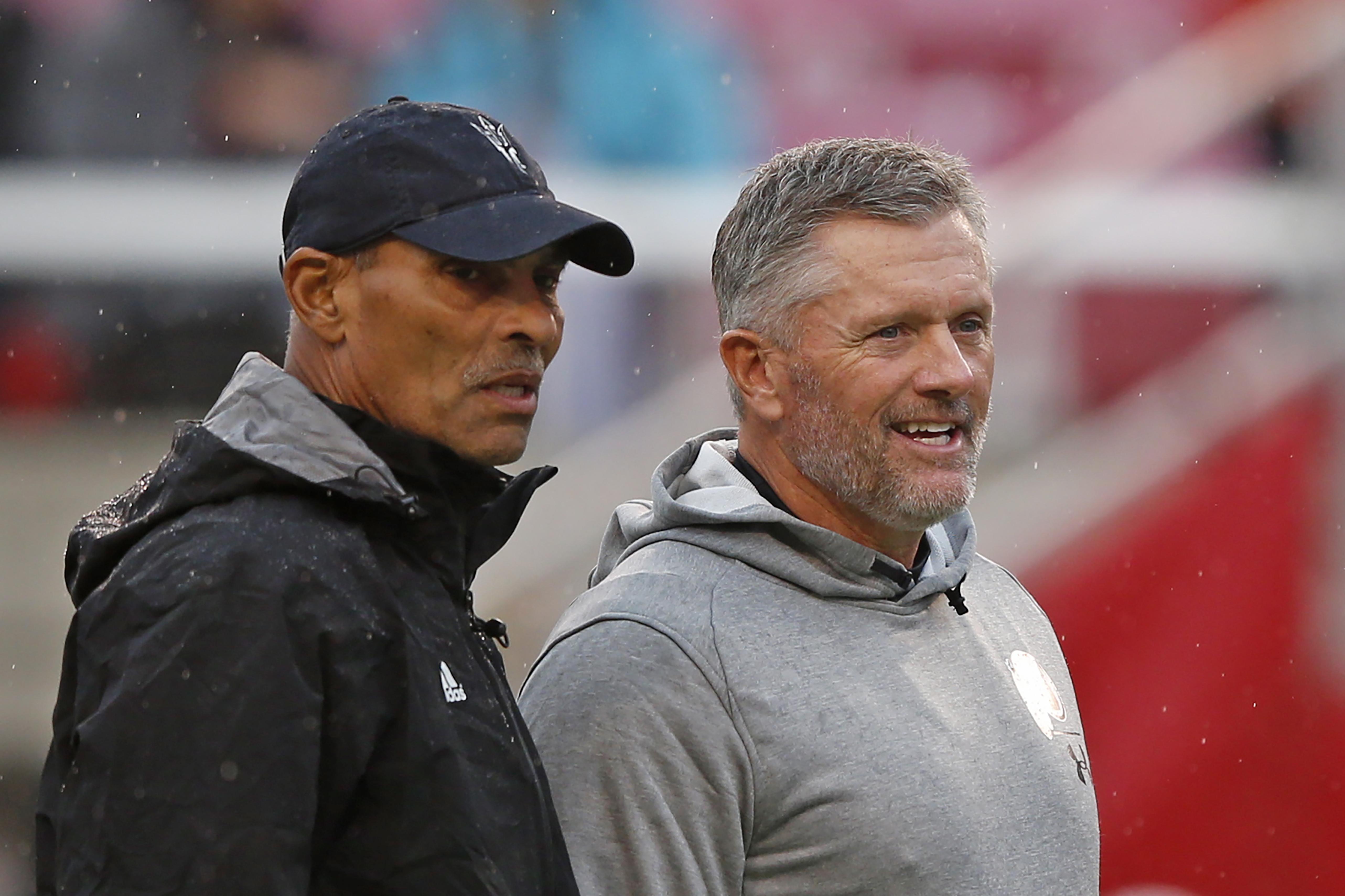 ASU coach Herm Edwards, left, and Utah coach Kyle Whittingham speak before a game Saturday, Oct. 19, 2019, in Salt Lake City.