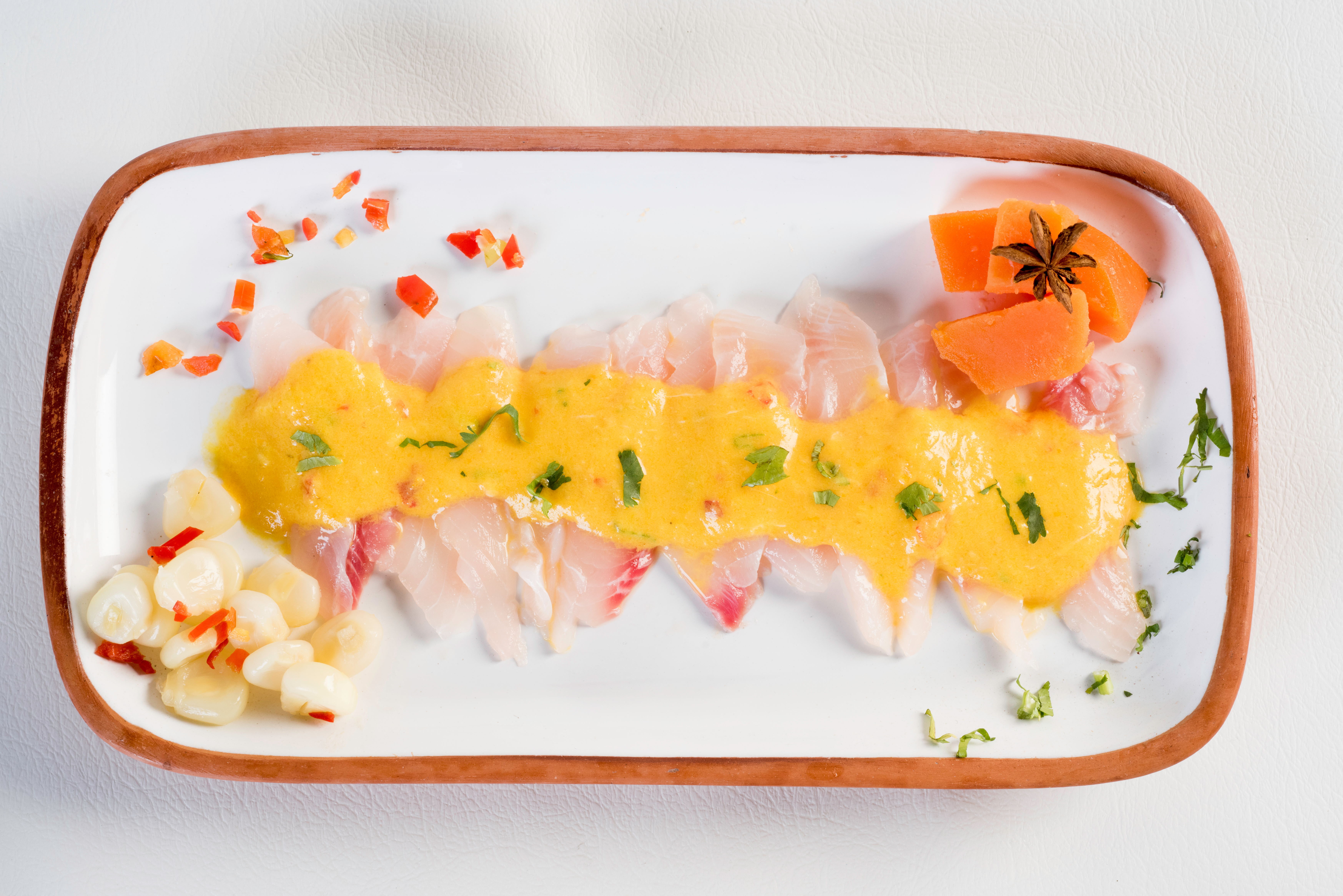 Slices of white fish sit on a platter, drizzled in a bright-yellow sauce.
