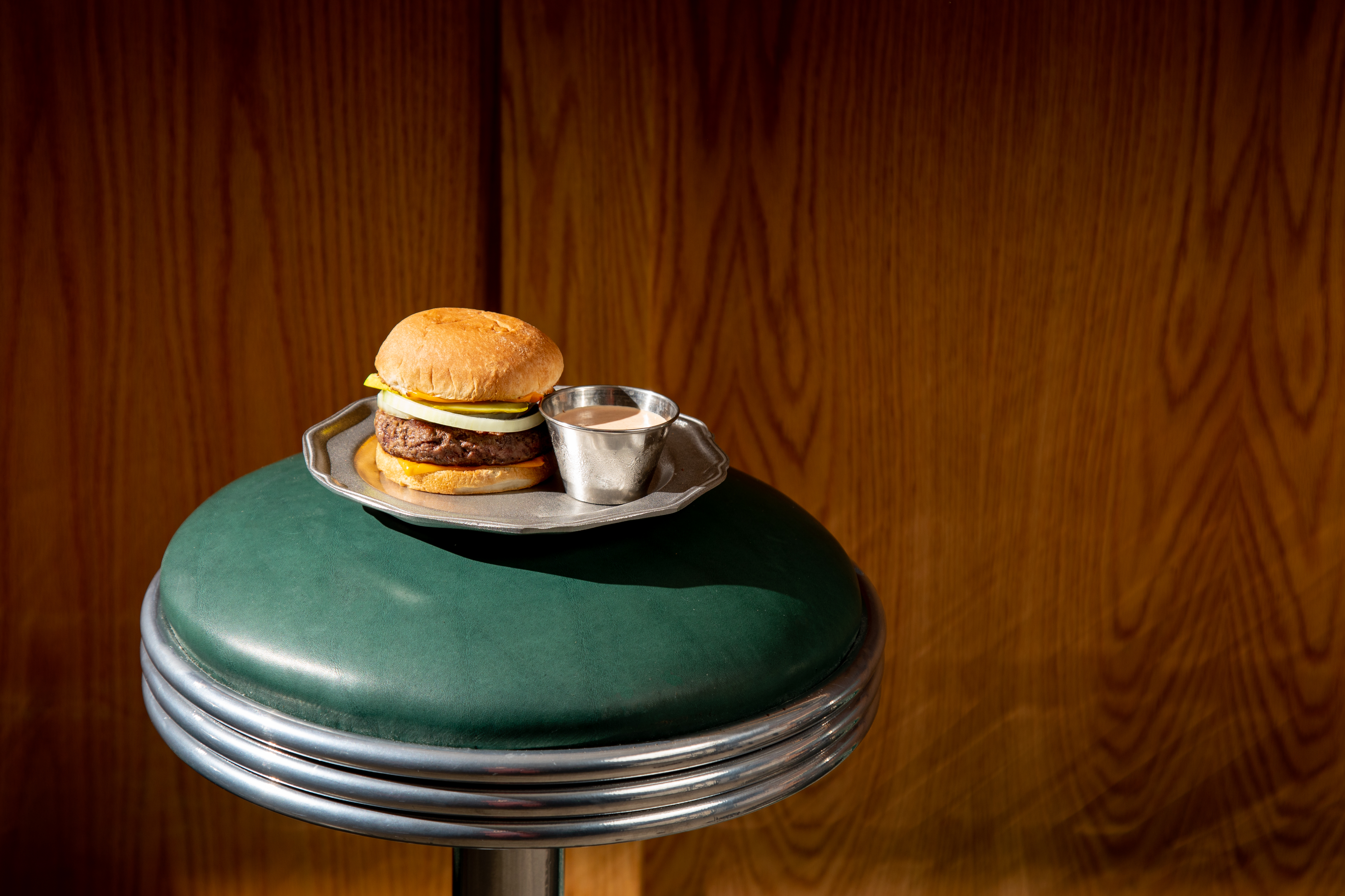 A traditional burger with sauce on the side on a silver platter is sitting on top of a green leather diner stool.