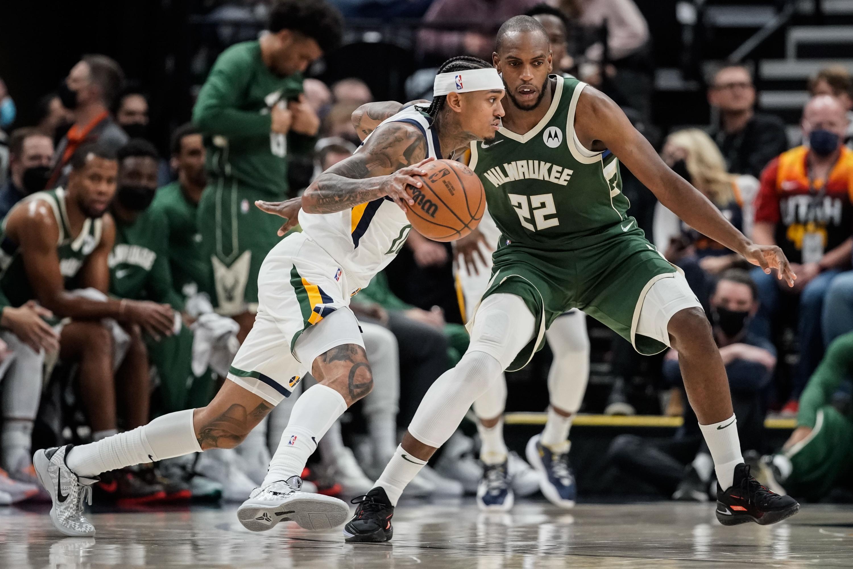 Utah Jazz's Jordan Clarkson, left, runs past Milwaukee forward Khris Middleton at Vivint Arena in Salt Lake City.