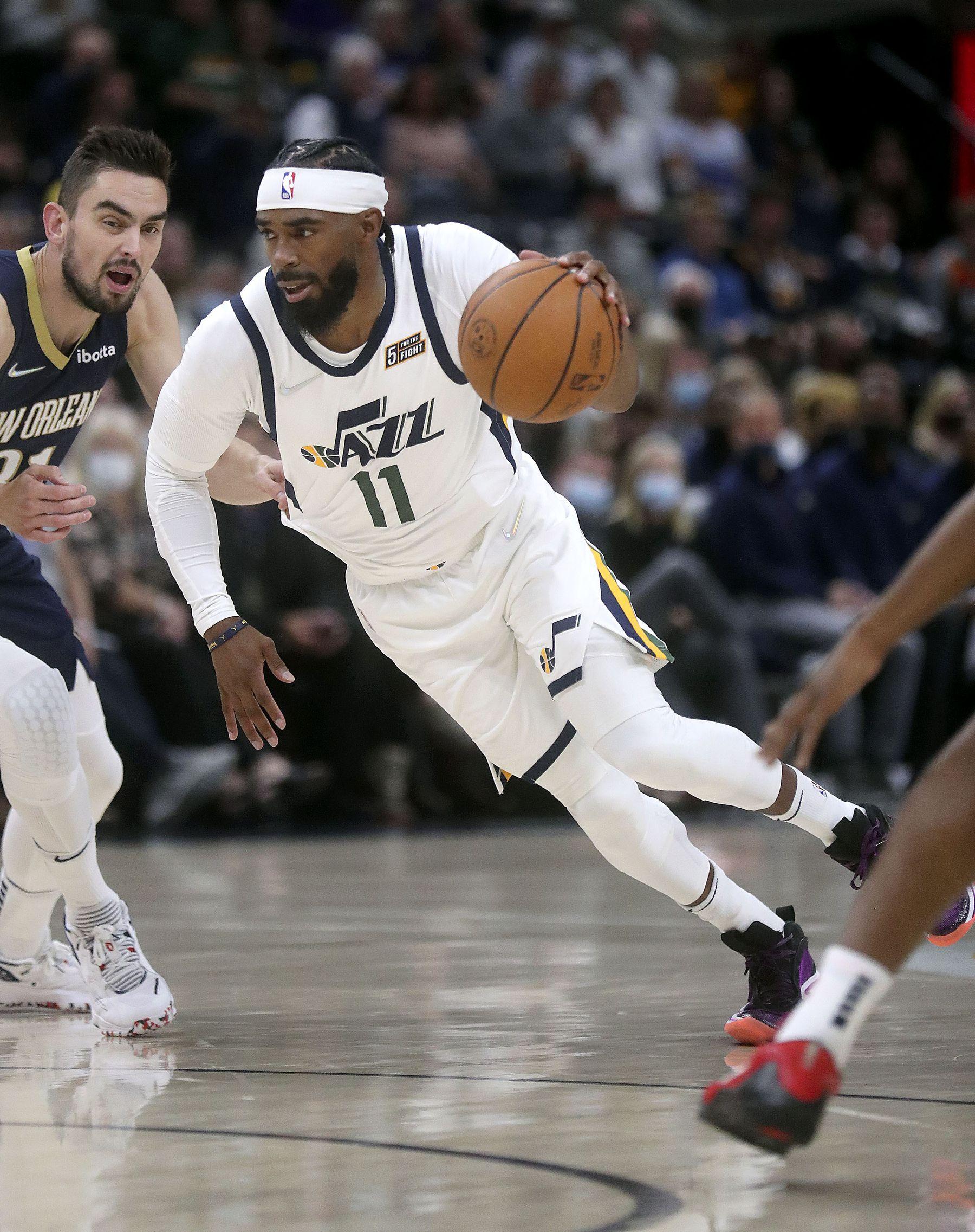 Utah Jazz guard Mike Conley (11) dribbles during a preseason NBA game against the New Orleans Pelicans.