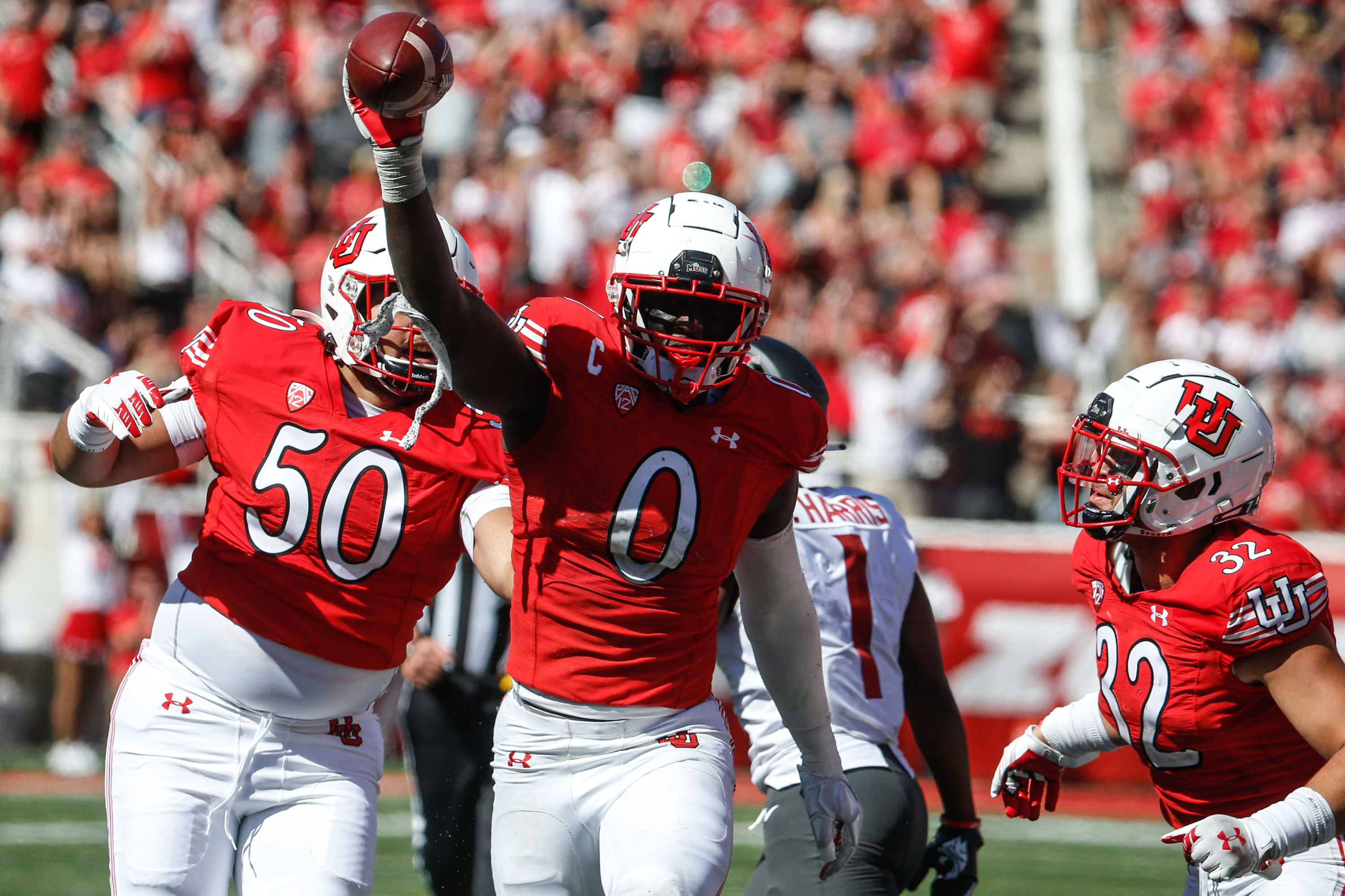 Utah linebacker Devin Lloyd holds the ball and celebrates with his teammates.