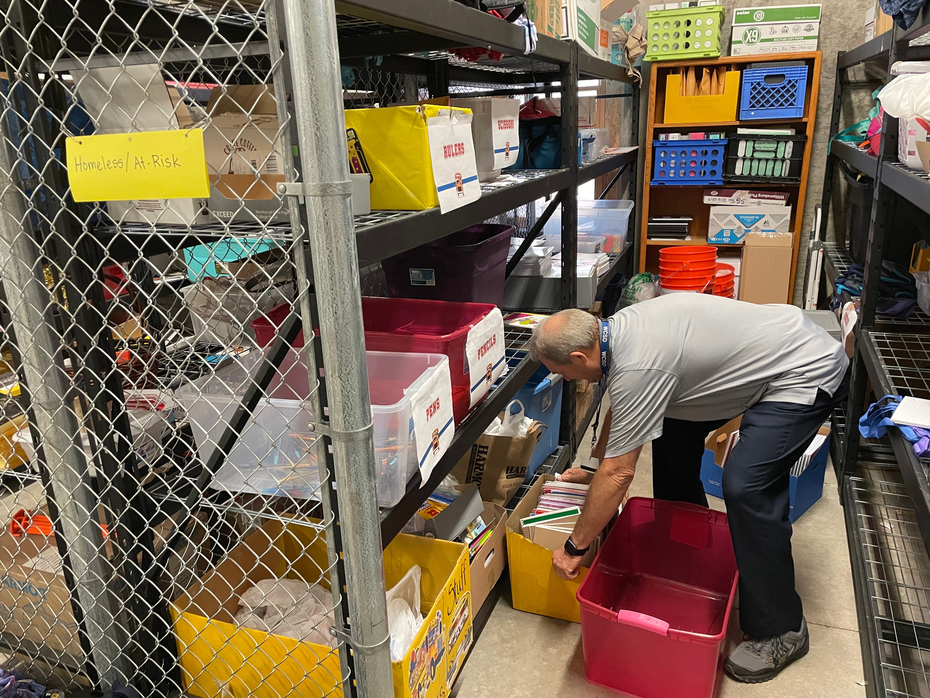 Mike Carr, homeless liaison for the Washington County School District, sorts through boxes of donated school supplies the week before classes resume in August. The school district's count of homeless students dropped by more than a third during the pandemic.