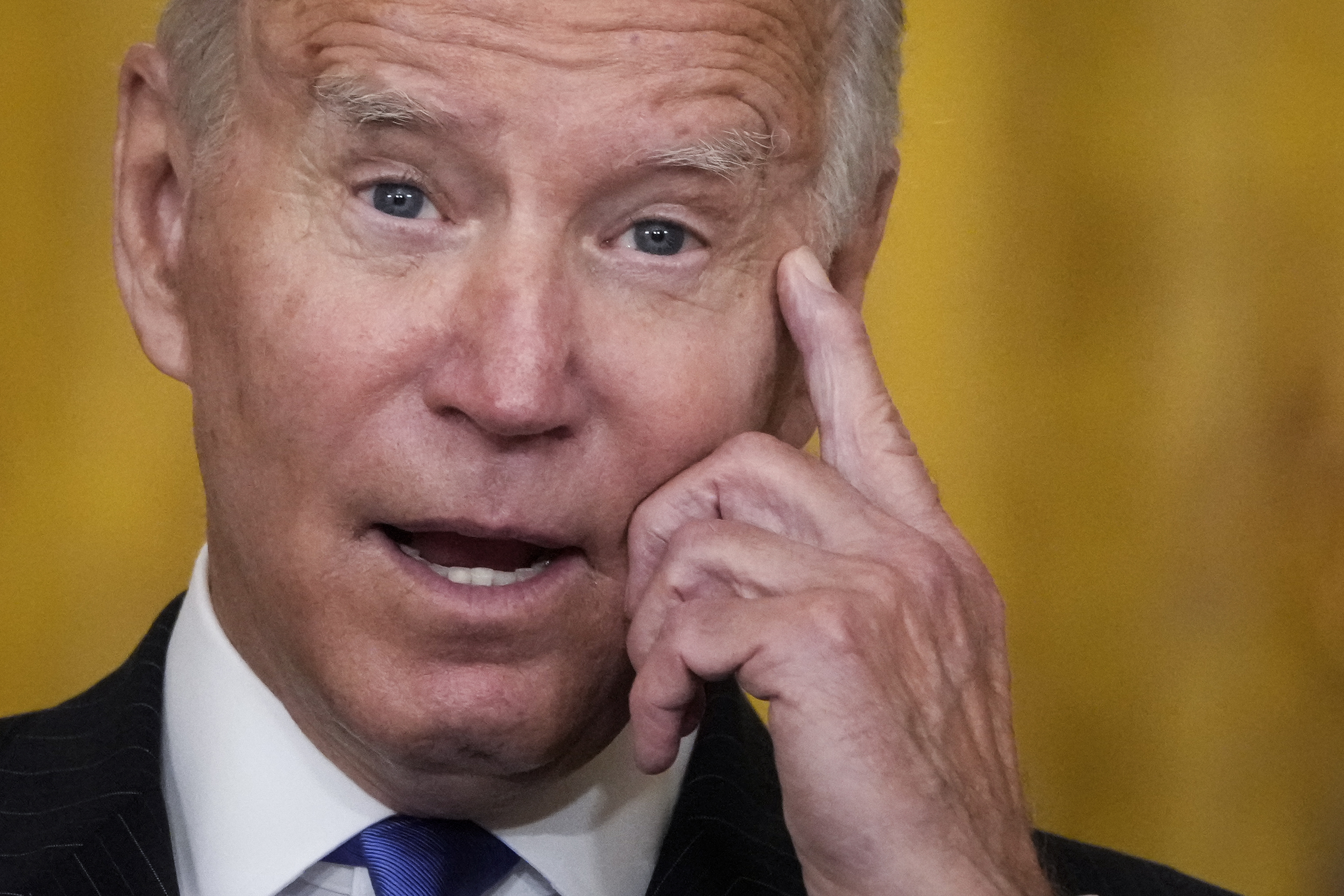President Joe Biden in closeup with his index finger to his temple.