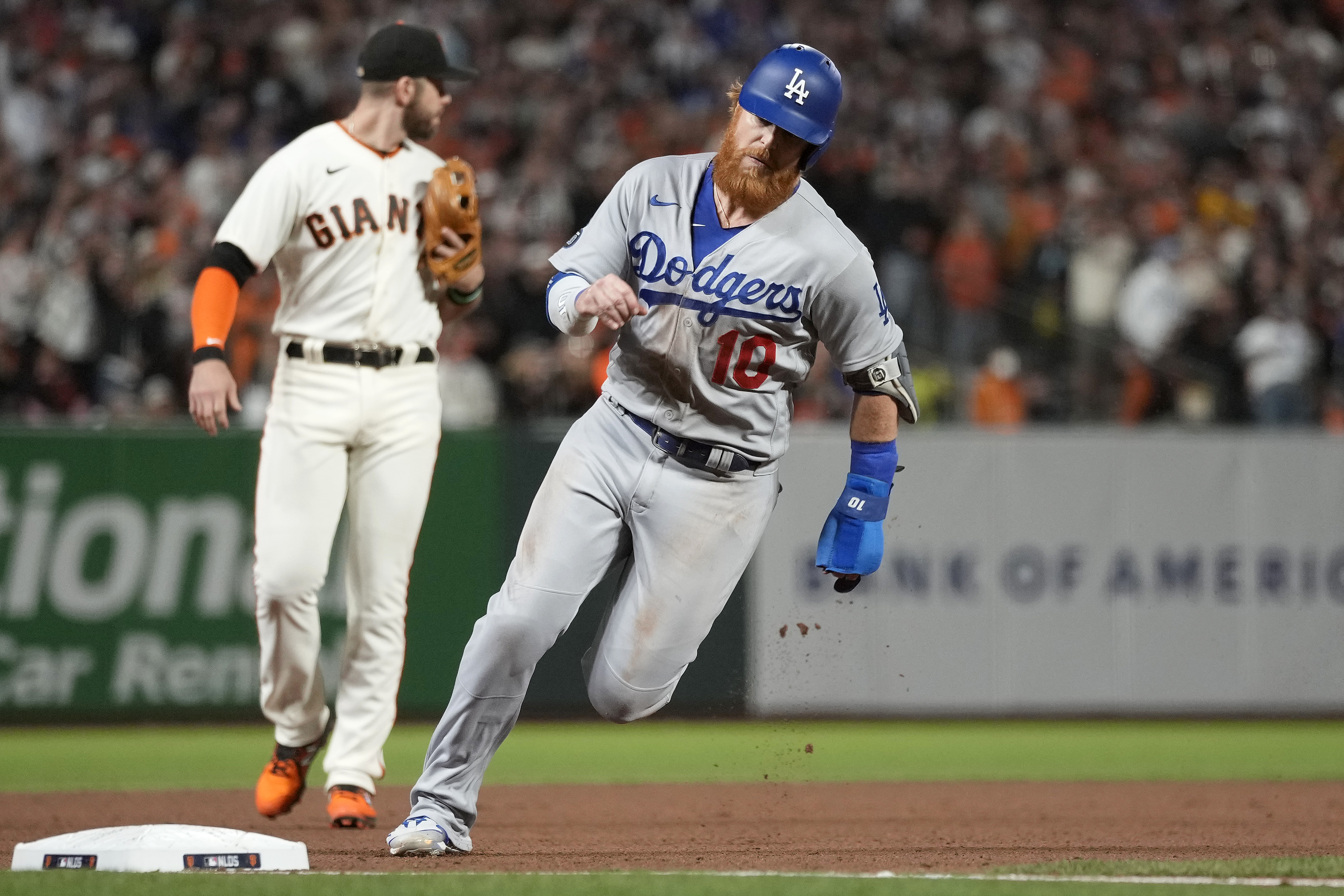 Justin Turner #10 of the Los Angeles Dodgers rounds third base to score on an RBI single by Cody Bellinger #35 against the San Francisco Giants during the ninth inning in game 5 of the National League Division Series at Oracle Park on October 14, 2021 in San Francisco, California.