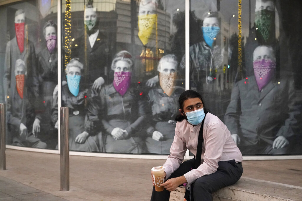A man sits in front of a COVID-19-themed mural in California.